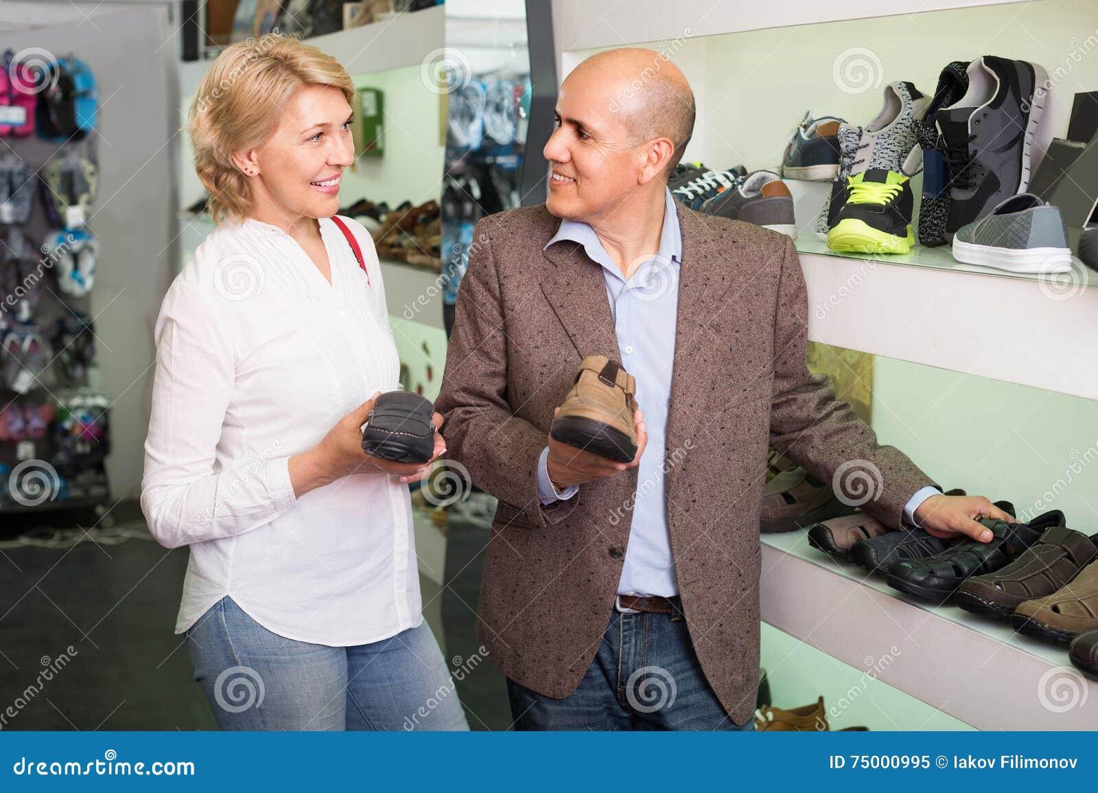 Twee gepensioneerden die samen paar schoenen voor mensen in schoensto kiezen