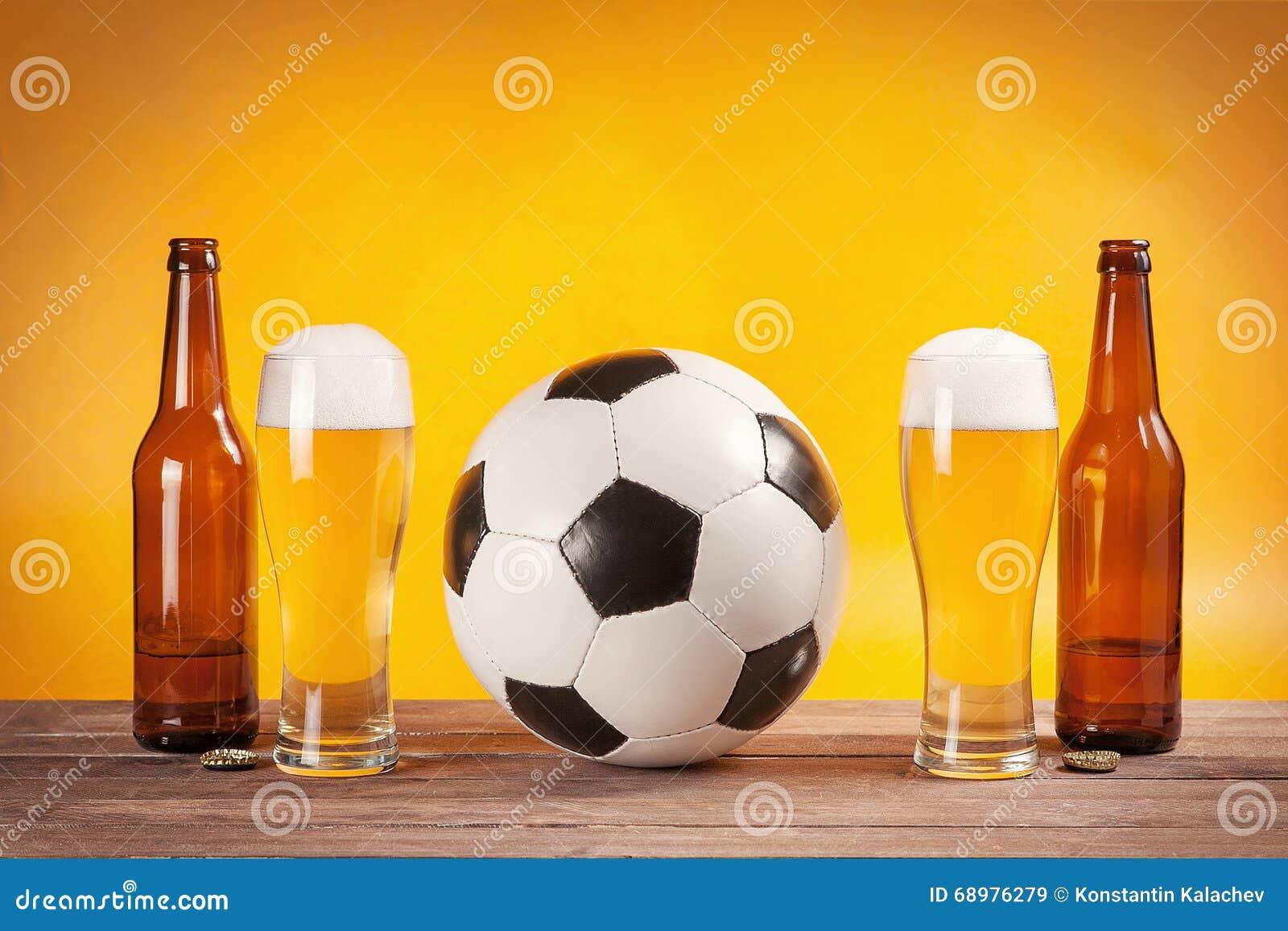 Twee glazen bier en flessen dichtbij voetbalbal