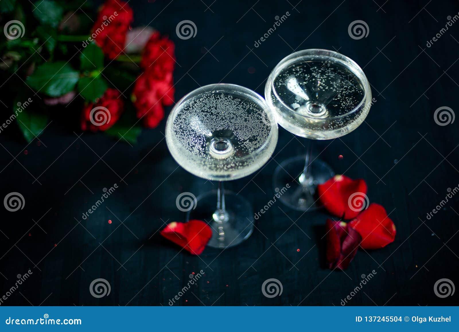 Twee glazen met witte champagne en bloemblaadjes van rode rozen op de zwarte achtergrond