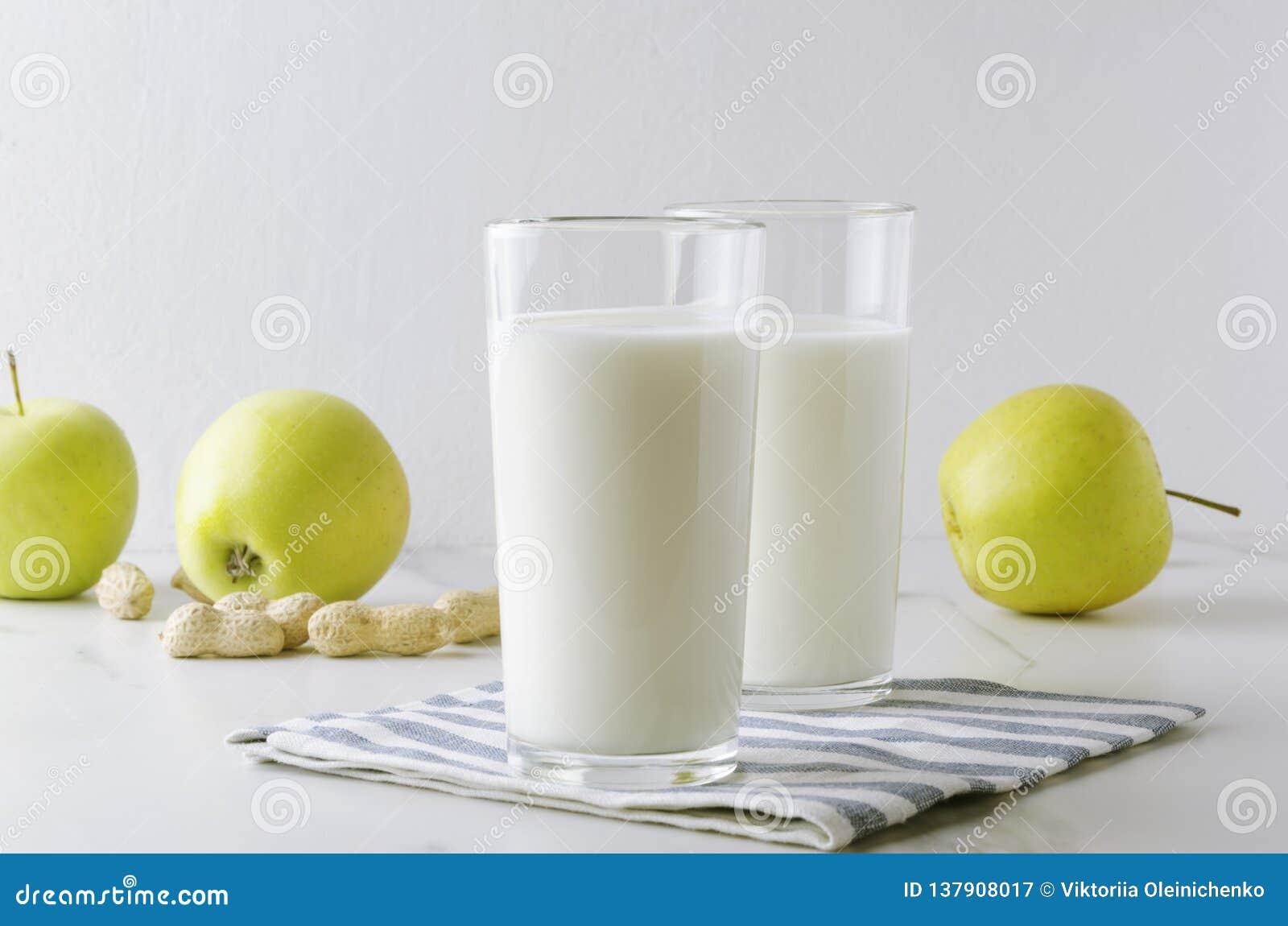 Twee glazen van kefir, aplles, noten, servet op witte lijst tegen witte achtergrond in de keuken Concept melkachtig dieet en gezo