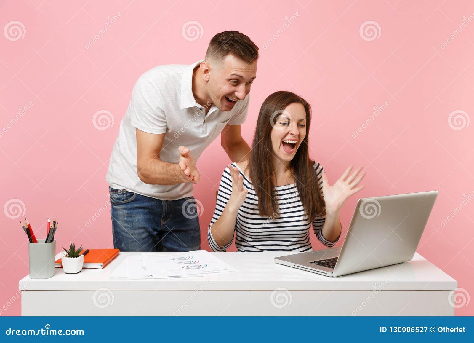 Twee glimlachende bedrijfsvrouwenman collega s zitten het werk bij wit bureau met eigentijdse laptop op pastelkleur roze achtergr