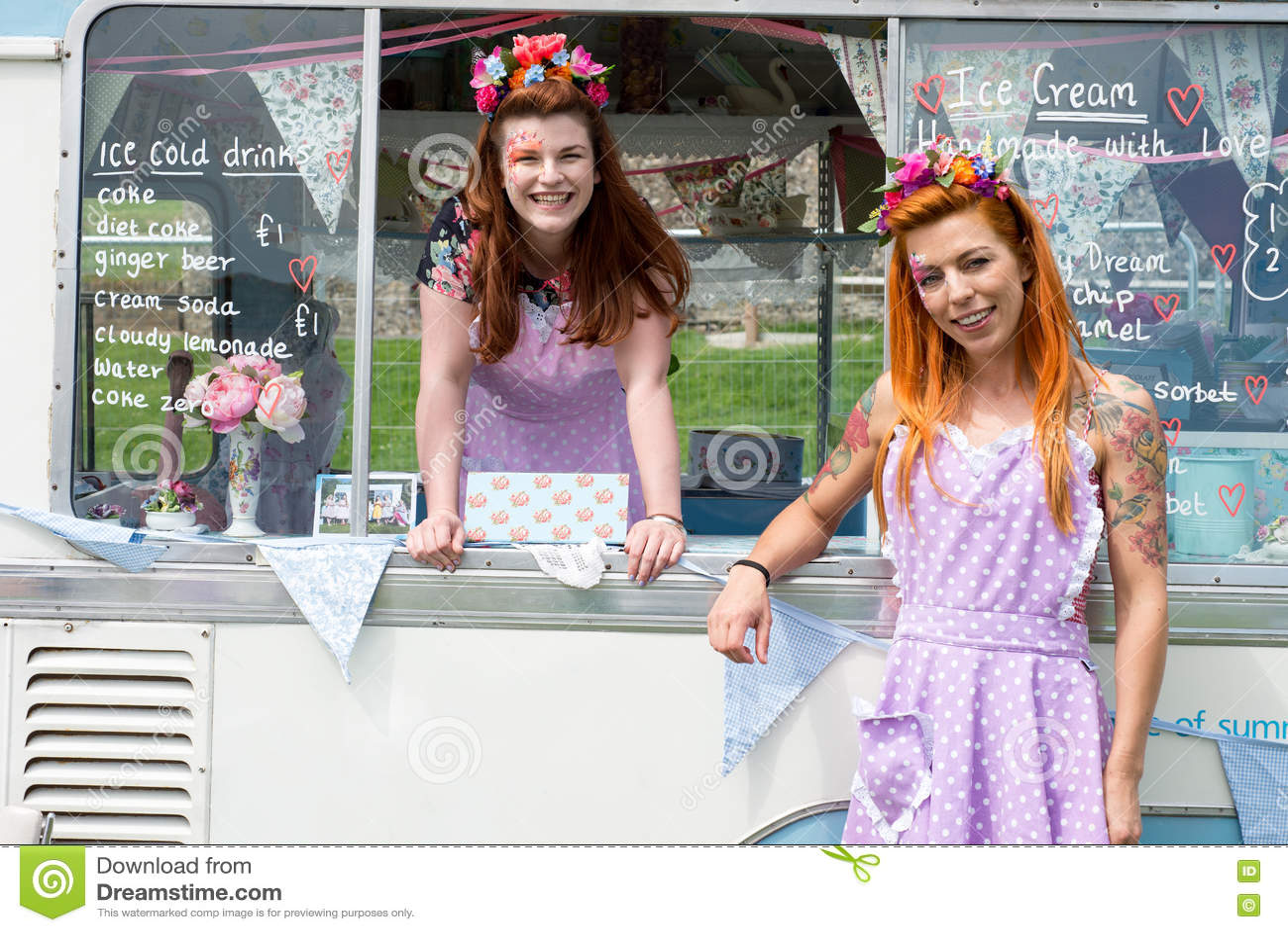 Twee glimlachende dames die uitstekende kleding met roomijsbestelwagen dragen