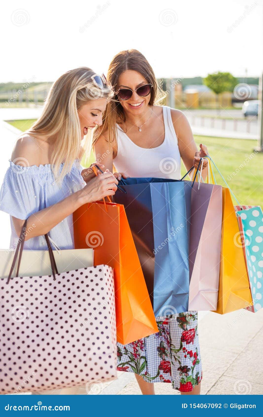 Twee glimlachende gelukkige jonge vrouwen die van het winkelen terugkeren