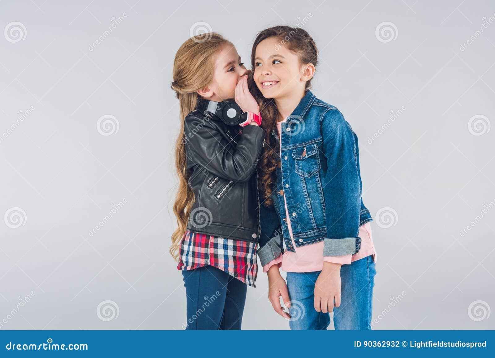 Twee glimlachende meisjes die geheimen fluisteren