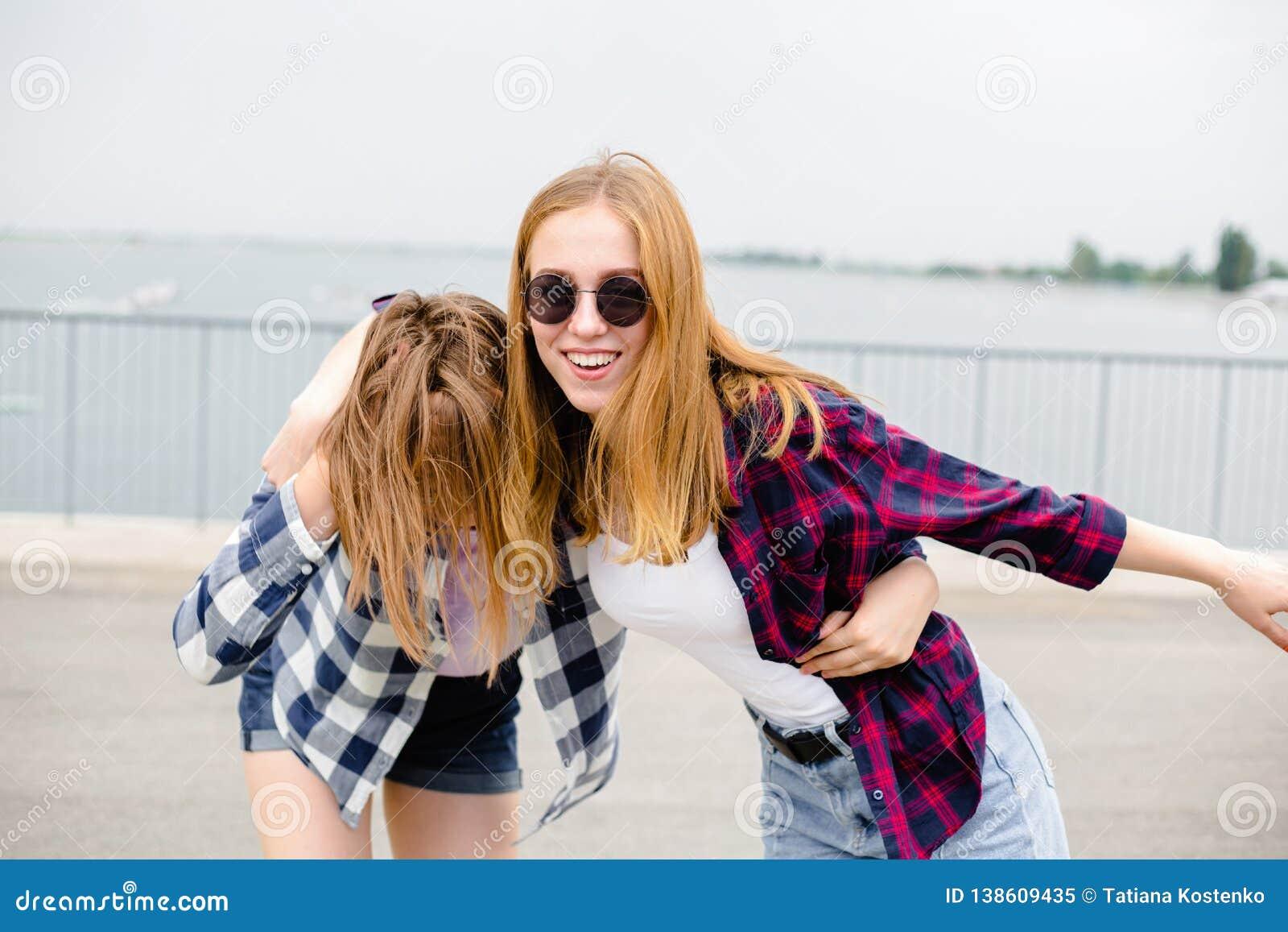 Twee glimlachende vrouwelijke vrienden die elkaar op de straat koesteren Vakantie, vakantie, liefde en vriendschapsconcept