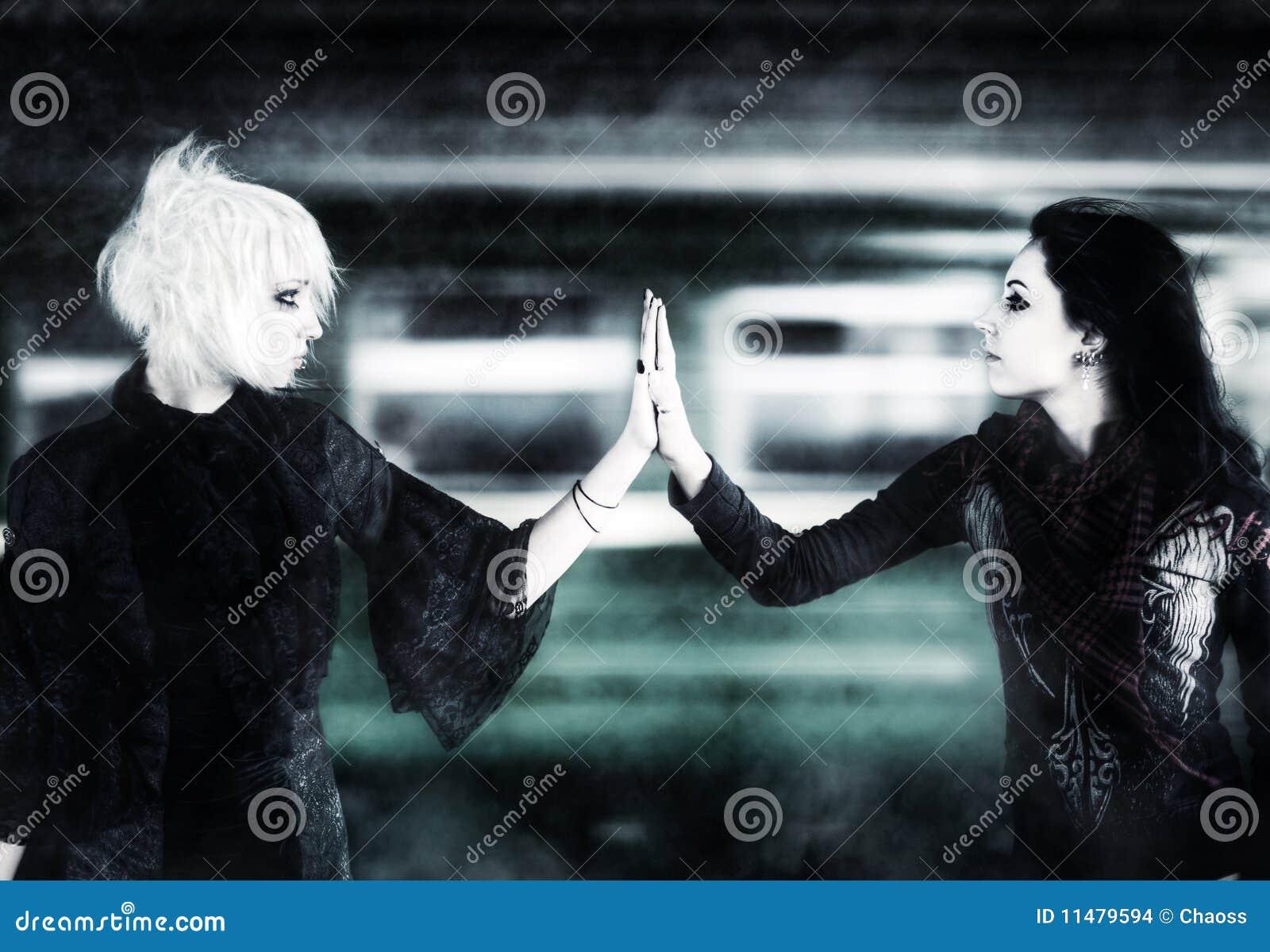 Twee gothvrouwen wat betreft handen