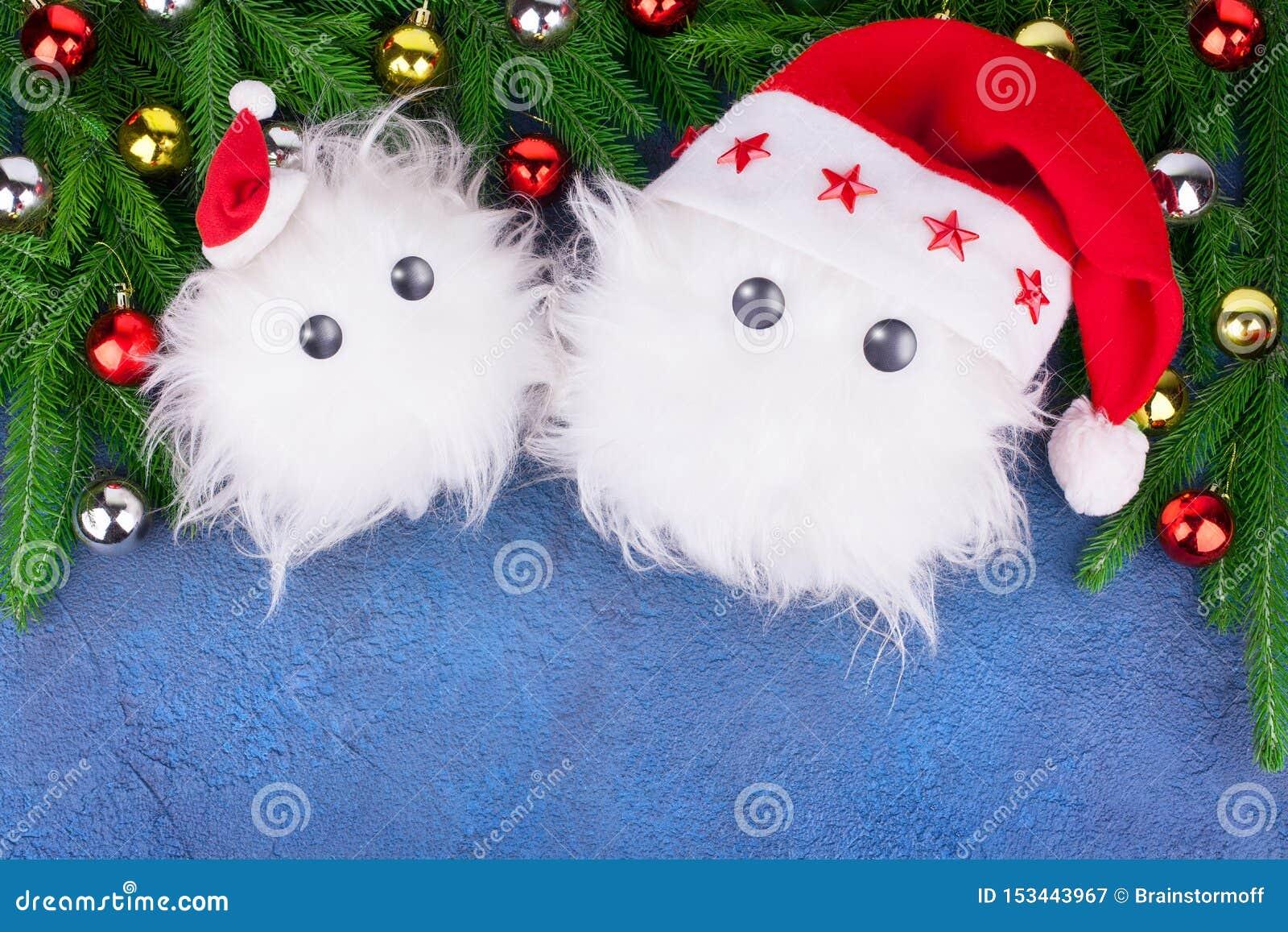 Twee grappig wit bontspeelgoed van de sneeuwmens in rode Santa Claus-hoeden, groene spar vertakt zich op blauwe leuke achtergrond