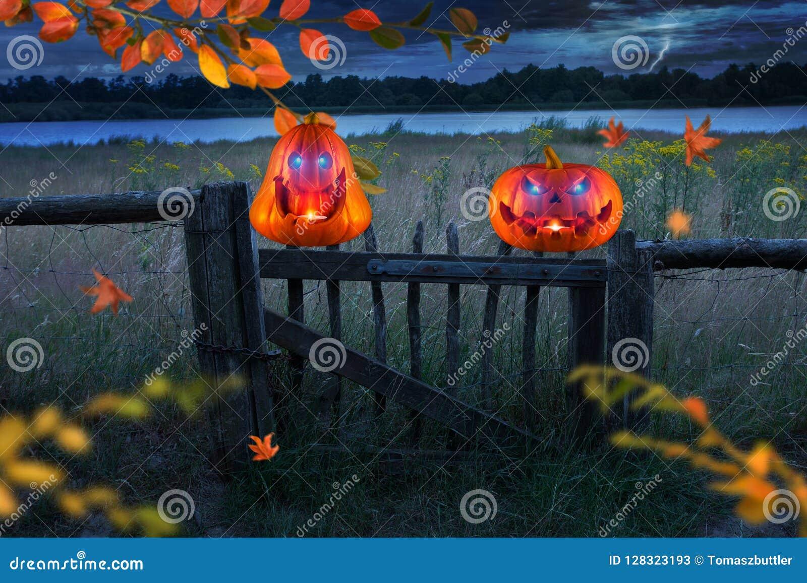 Twee grappige enge oranje pompoenen met gloeiende ogen op houten omheining bij Halloween-onweersbuinacht