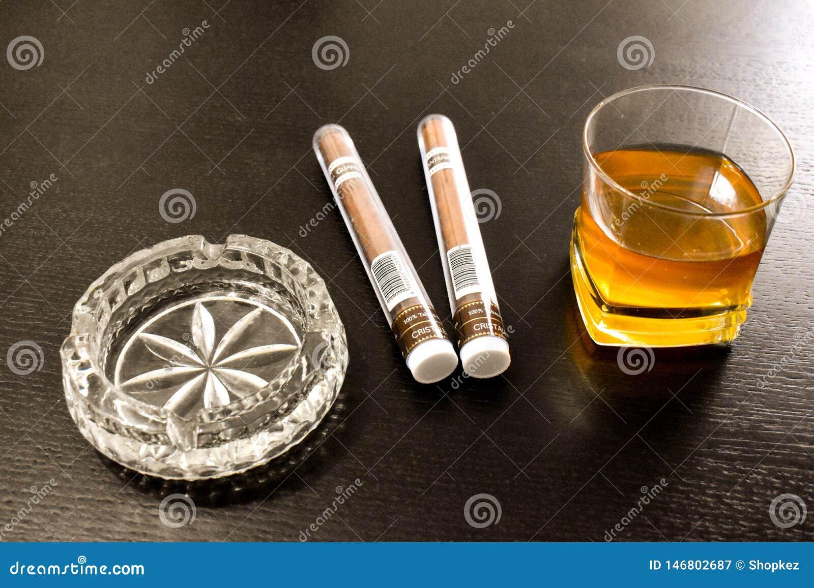 Twee grote sigaren, een kristalasbakje en een glas wisky op de zwarte lijst Boekarest, Roemenië - 03 04 2019