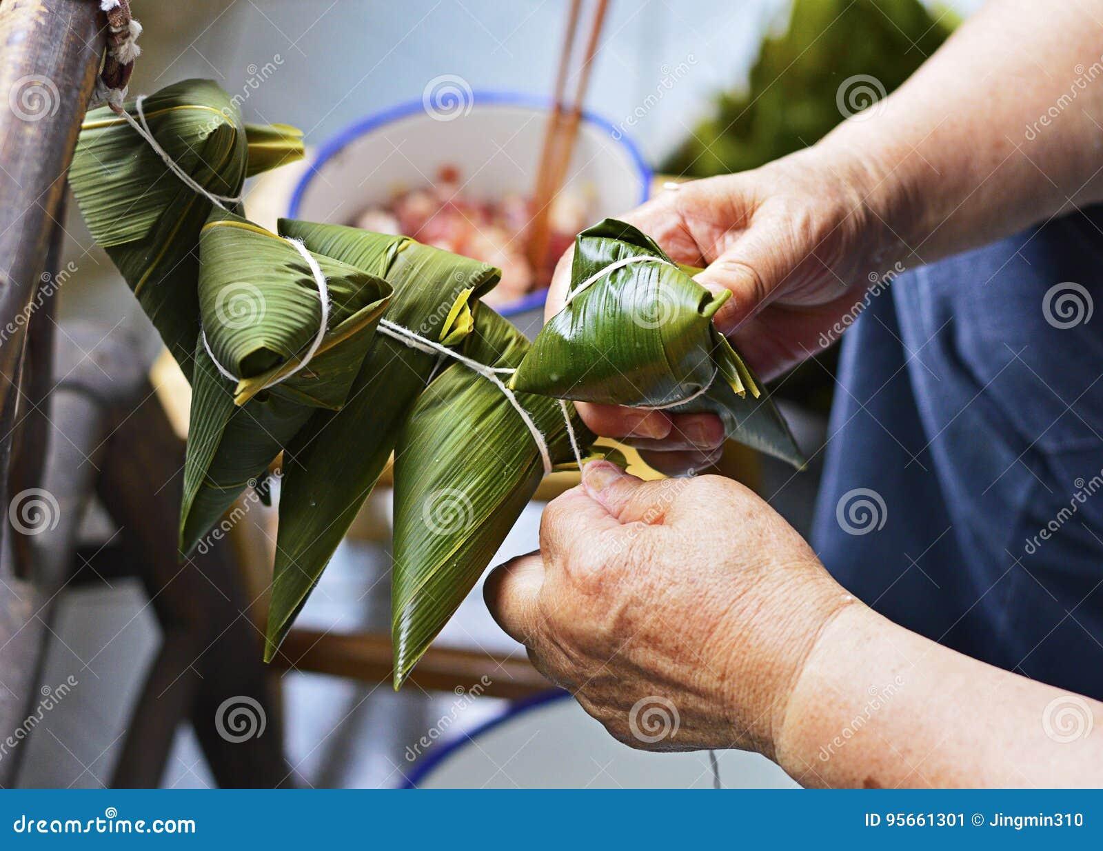 Twee Handen halen het Koord over het Blad aan om Zongzi, Traditionele Chinese Rijstbollen voor Dragon Boat Festival te maken