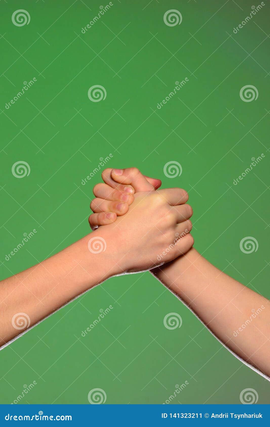 Twee handenhanddruk, die op een groene achtergrond wordt geïsoleerd, die vriendschap en verzoening symboliseren