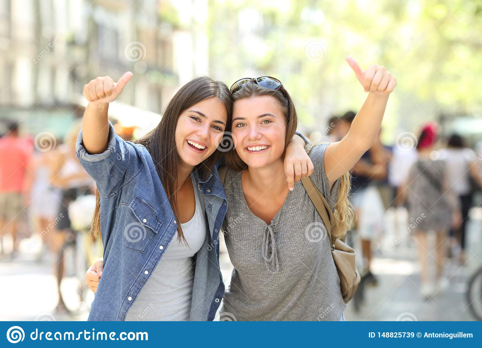 Twee het gelukkige vrienden beduimelt gesturing omhoog samen