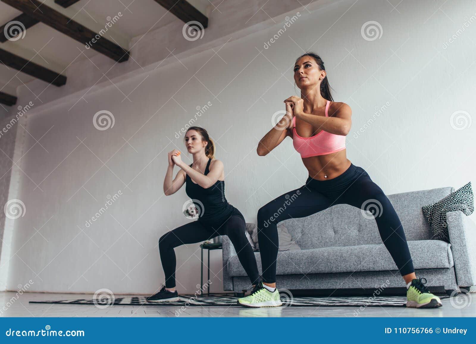 Twee het geschikte vrouwen hurkt doen thuis Vrouwelijke trainingsport en fitness