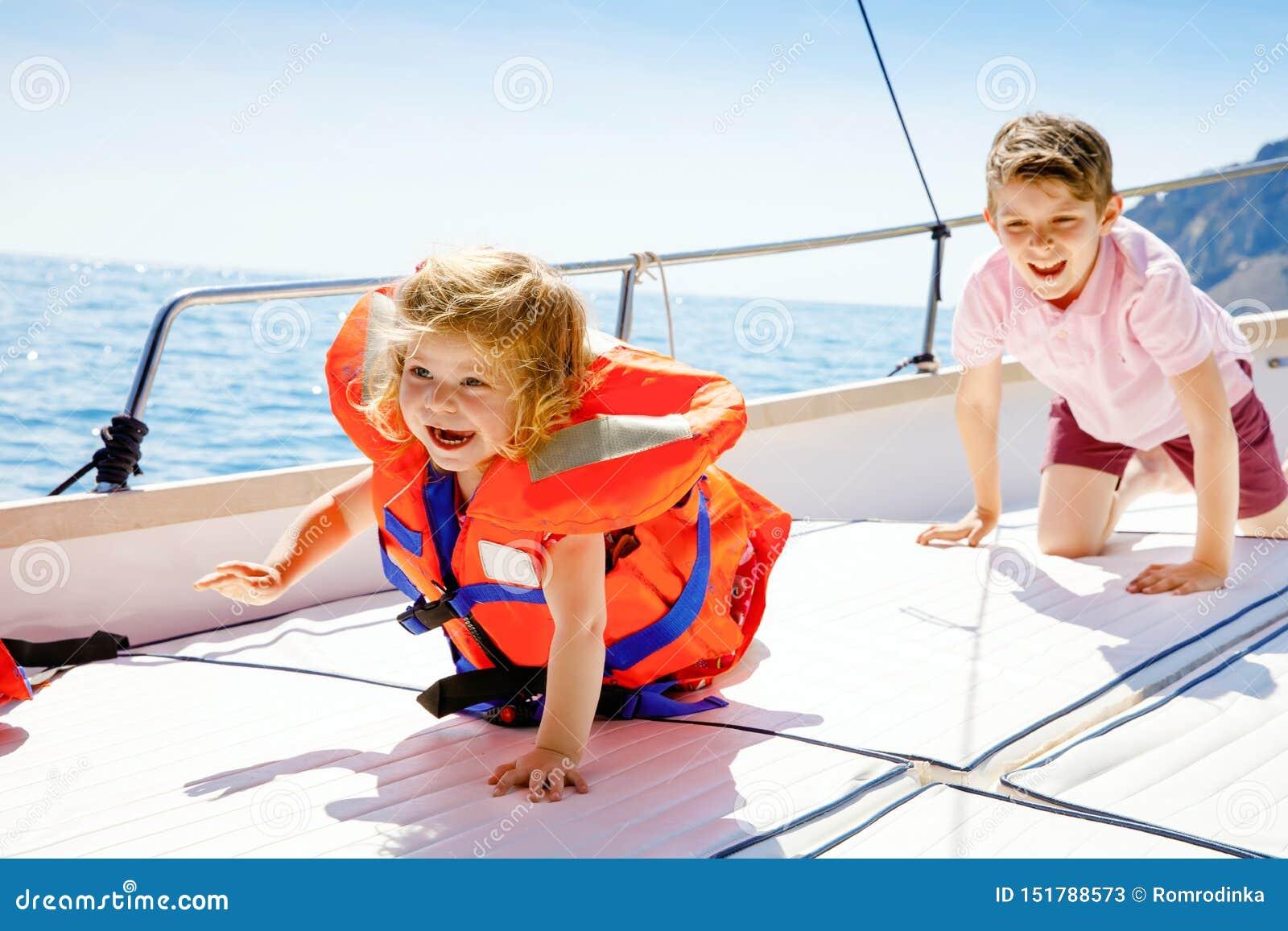 Twee het kleine van de jong geitjejongens en peuter meisje genieten die rondvaart varen Familievakanties op oceaan of overzees op
