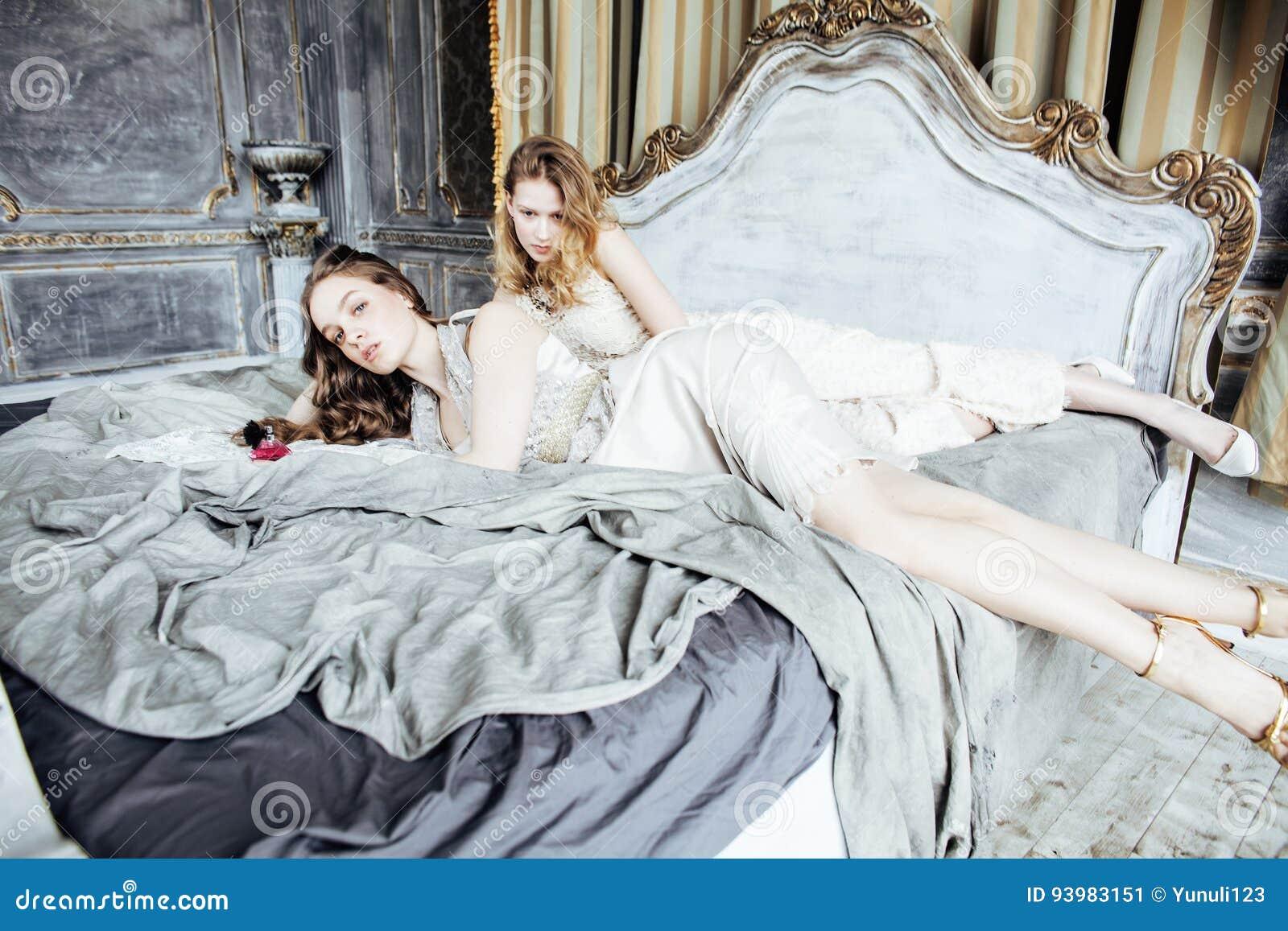 Twee het vrij tweelingmeisje van het zuster blonde krullende kapsel in het binnenland van het luxehuis samen, rijk jongerenconcep