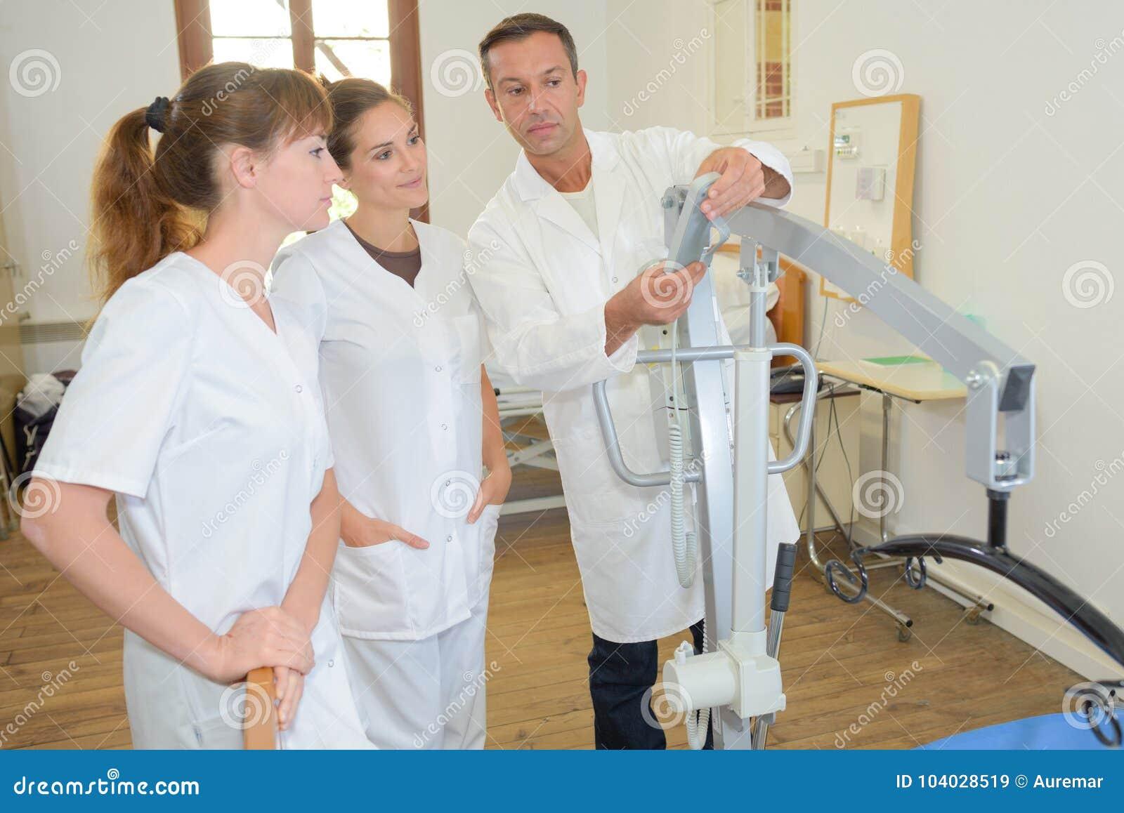 Twee homecareverpleegsters die leren hoe te hijstoestel te gebruiken