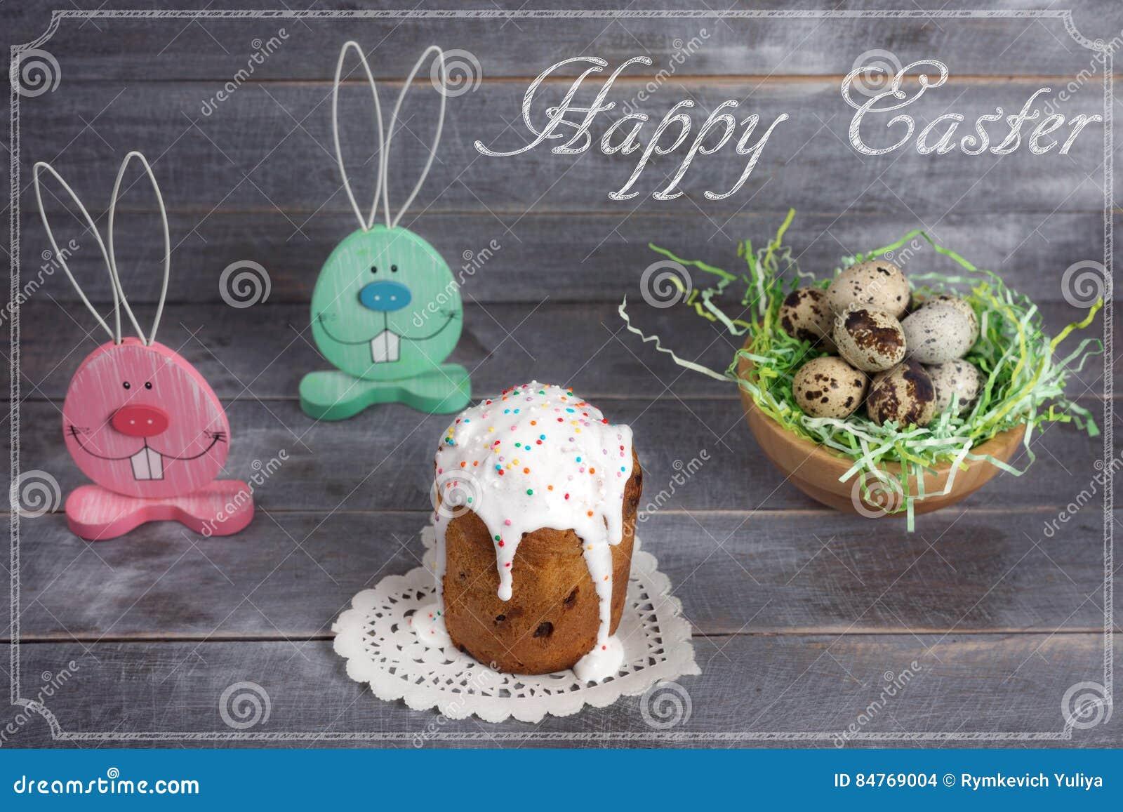 Twee houten konijn, een nest met kwartelseieren en Pasen-cakes met