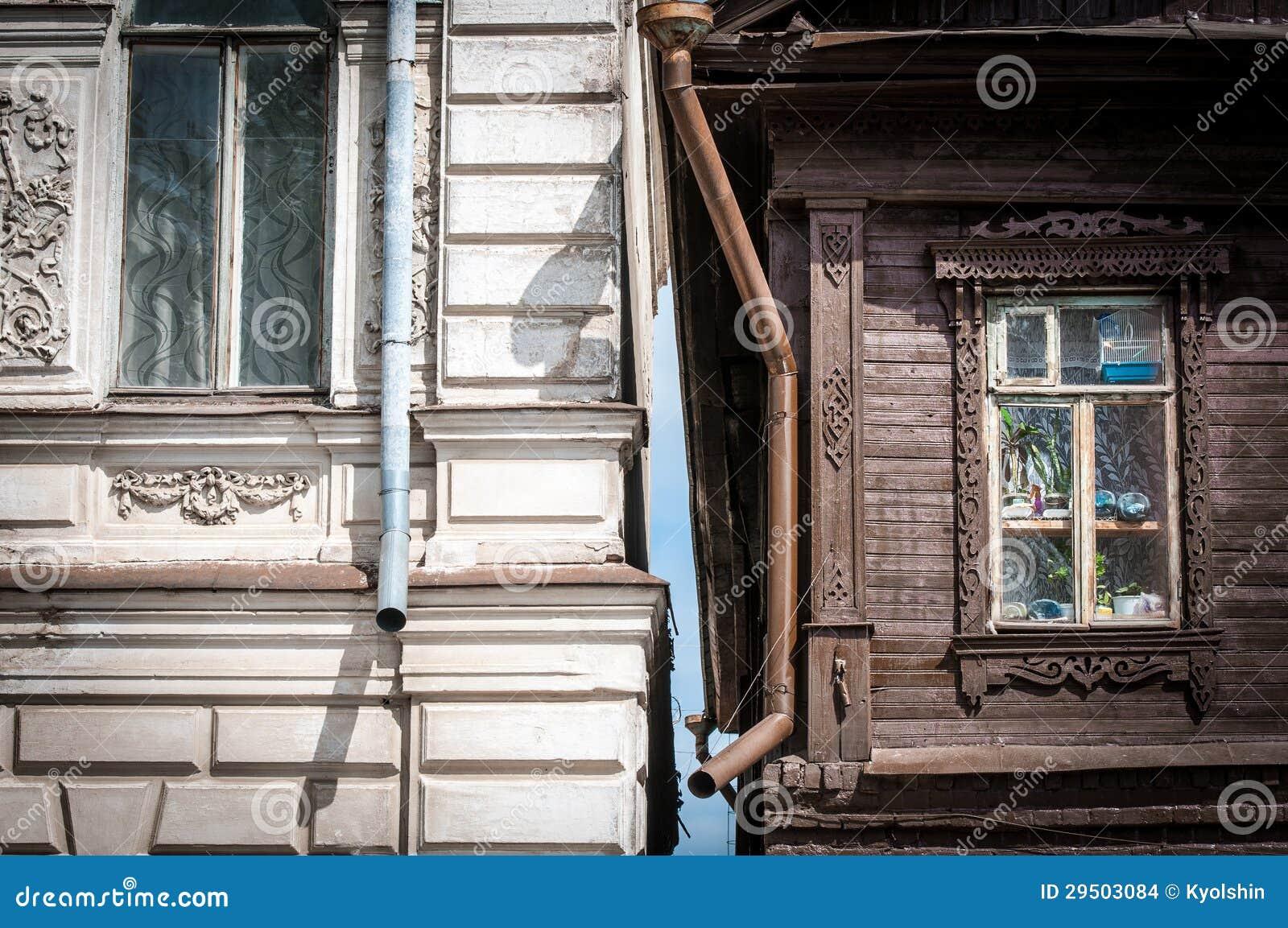 Twee huizen in Rusland: oude houten en baksteen.