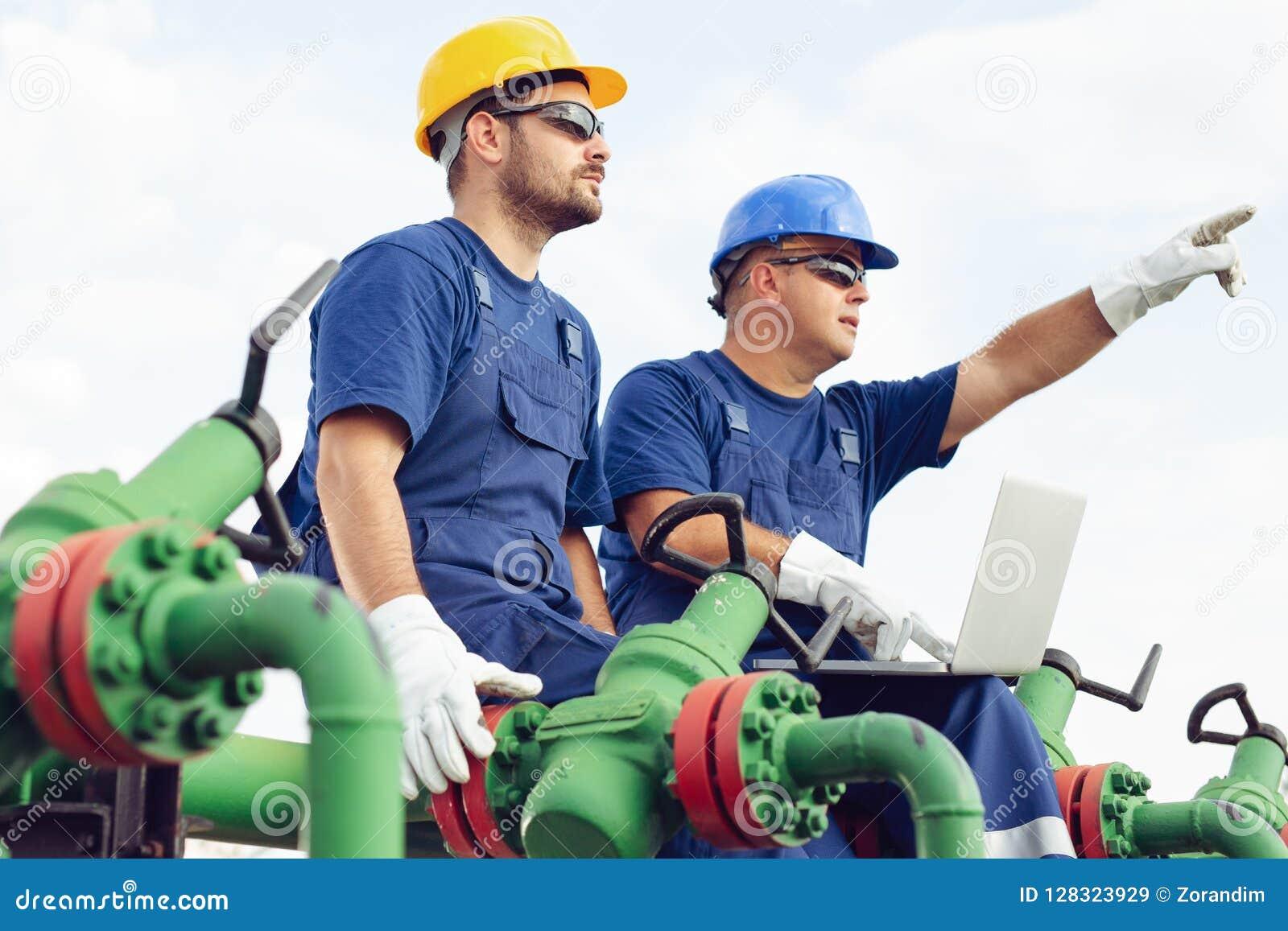 Twee ingenieurs die binnen olie en gasraffinaderij werken