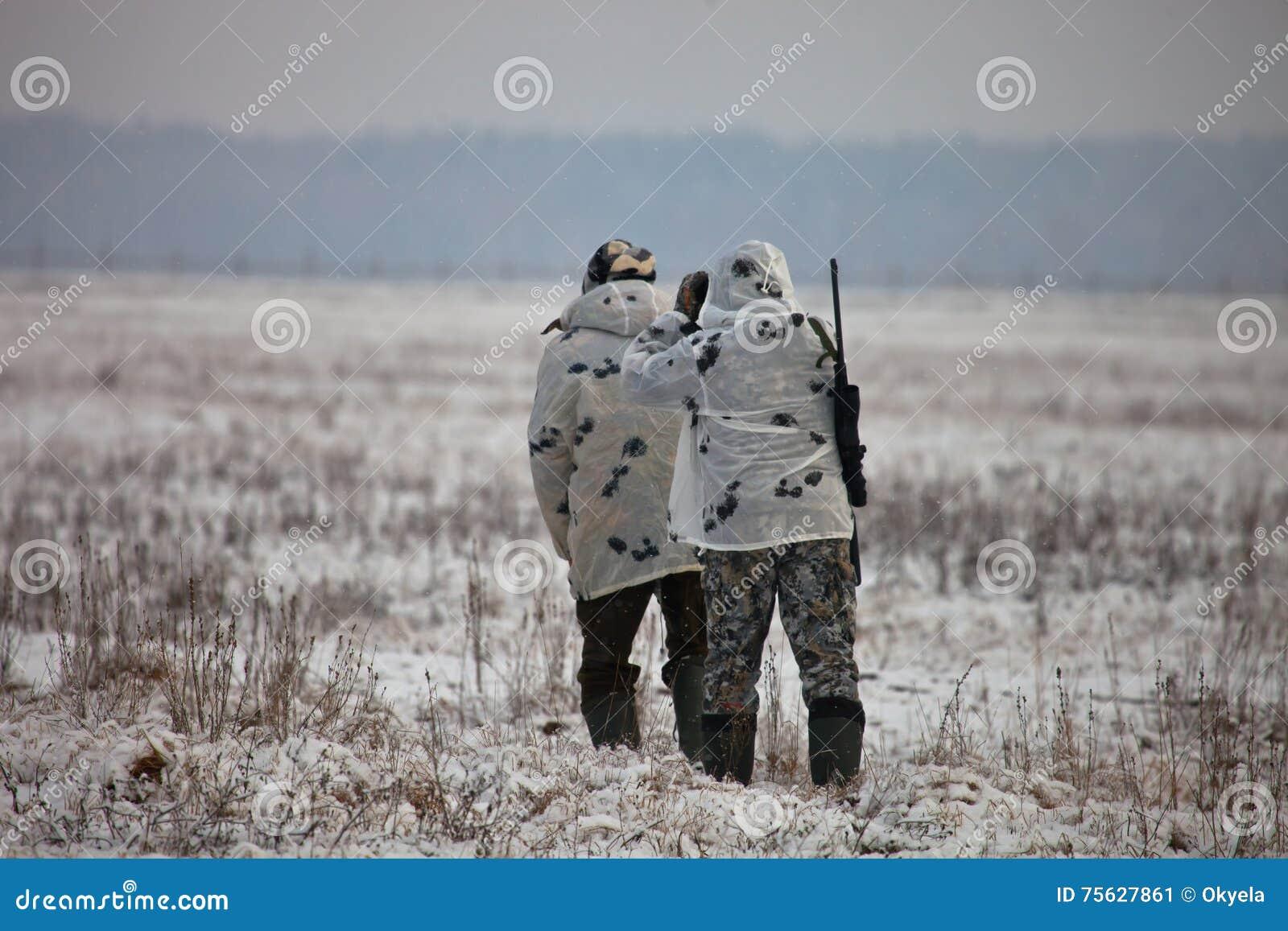 Twee jagers in de winter camoufleren om omhoog op het gebied heimelijk te nemen