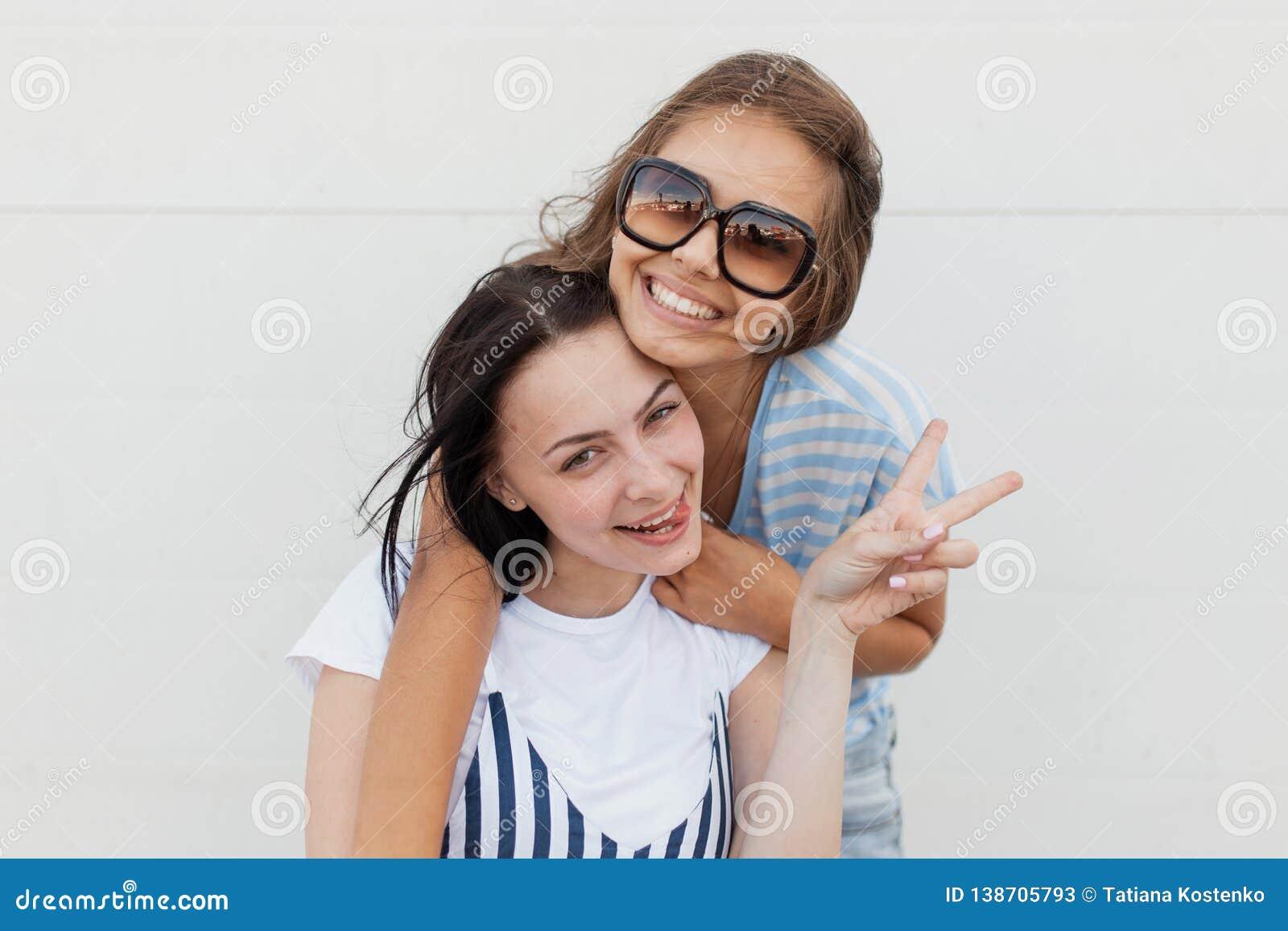 Twee jeugdige donker-haired meisjes, die toevallige uitrusting, mooie omhelzing dragen elkaar en bekijkend de camera