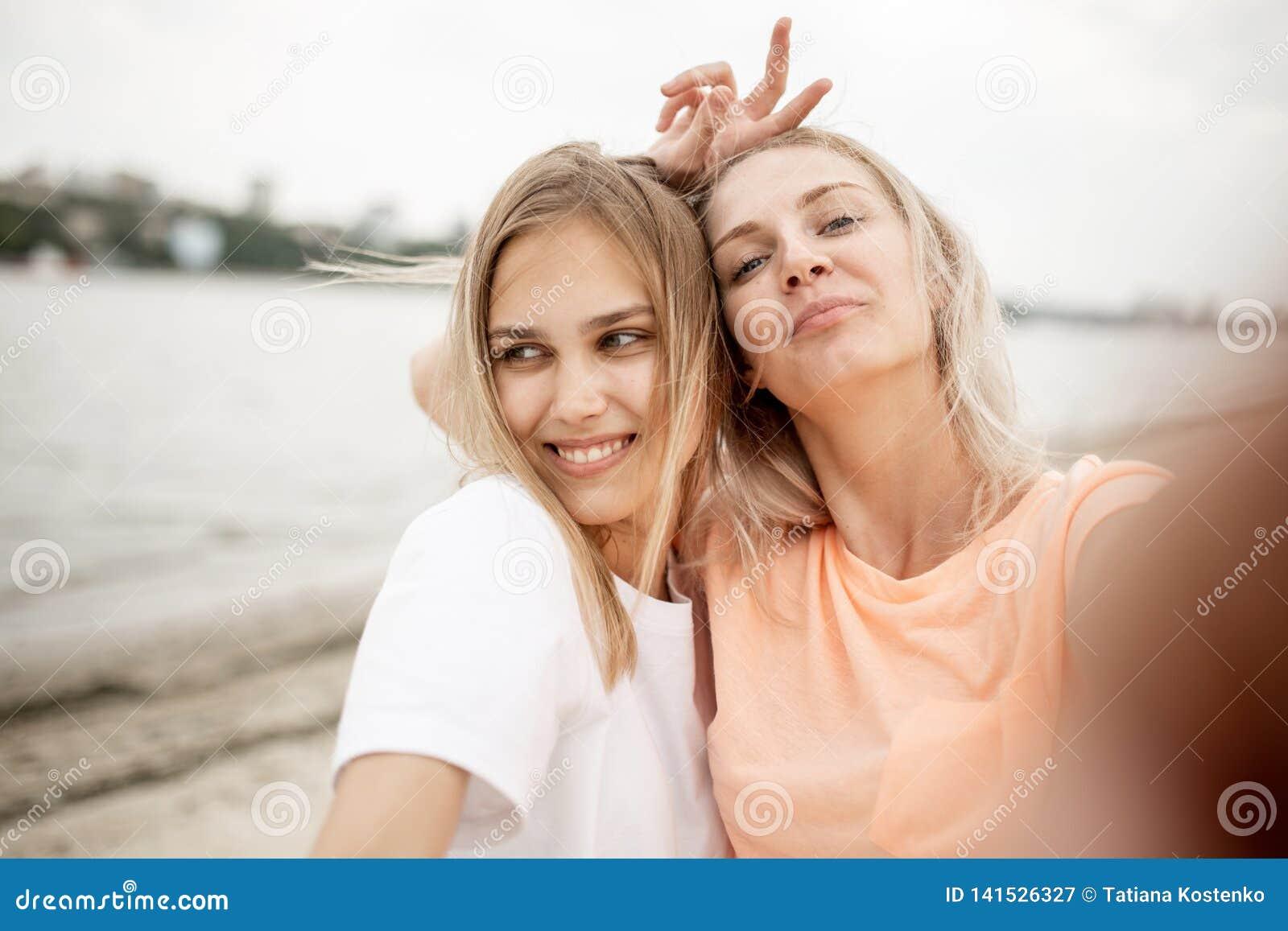 Twee jonge aantrekkelijke blondemeisjes nemen een selfie op het strand op een warme winderige dag