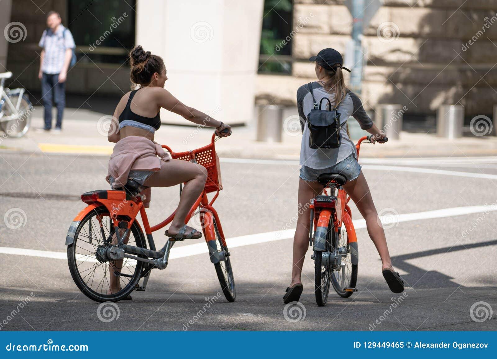 Twee jonge aantrekkelijke wijfjes op fietsen