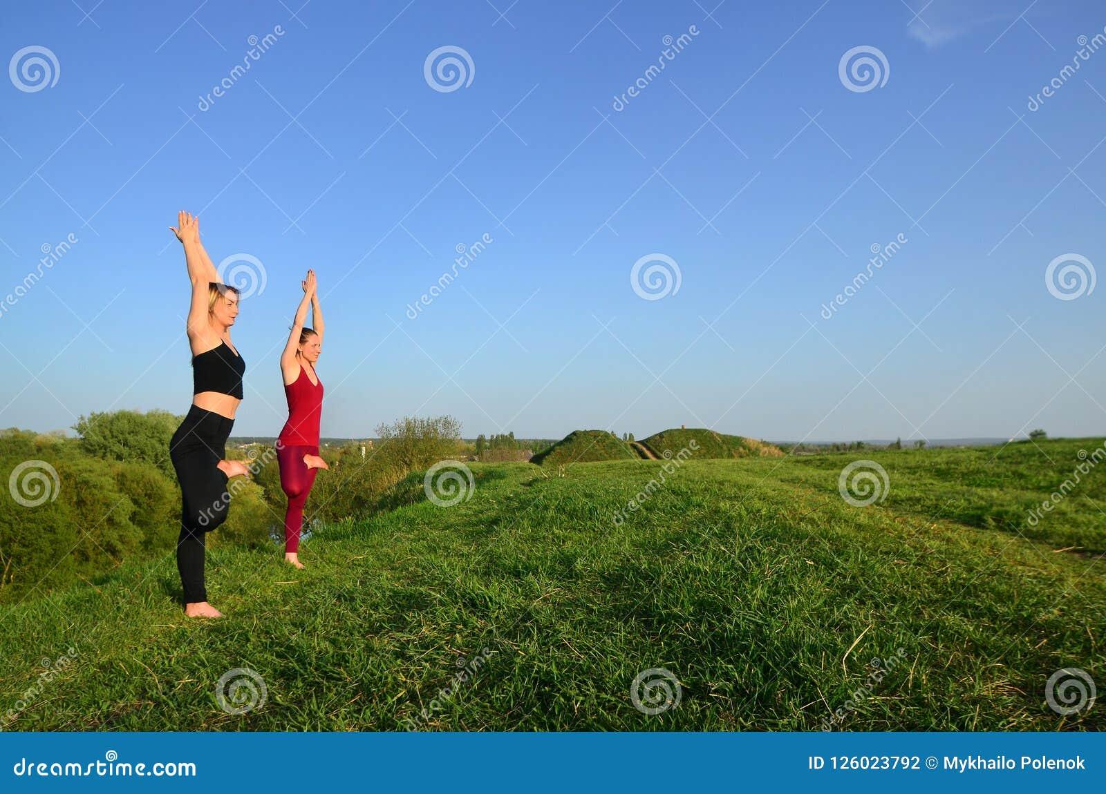 Twee jonge blonde meisjes in sporten past praktijkyoga op een schilderachtige groene heuvel aan