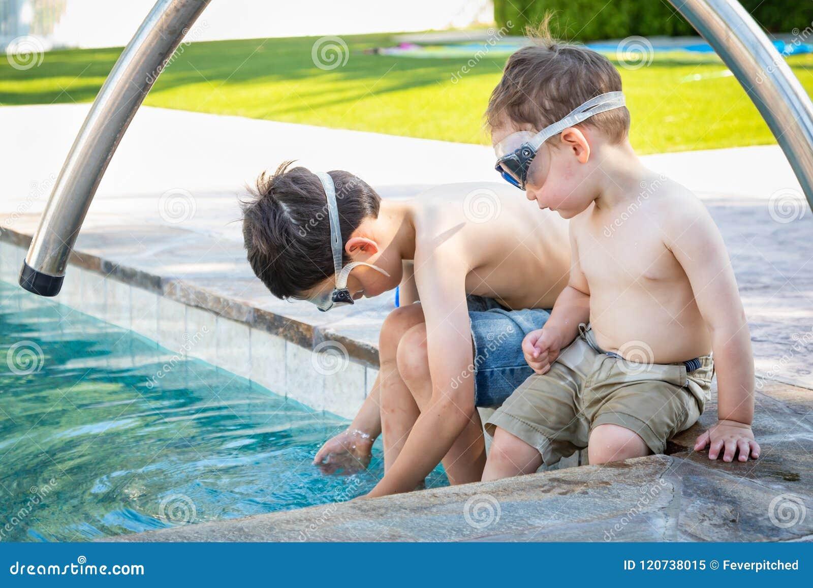 Twee Jonge Chinese Kaukasische Broers door de Pool die Zwemmende Beschermende brillen dragen