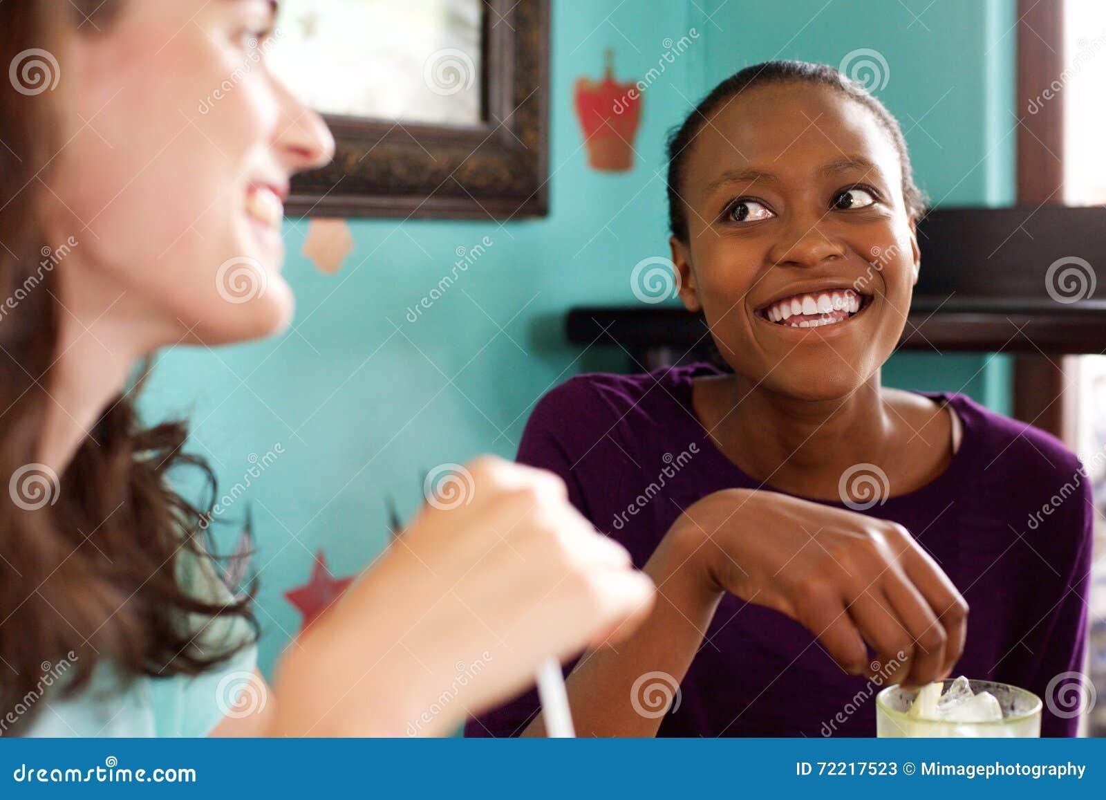 Twee jonge dames die in een koffie babbelen