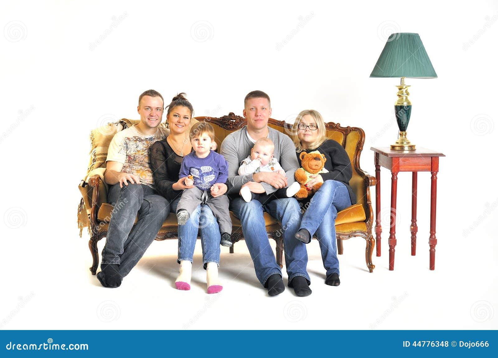 Twee jonge families spelen de dwaas met een kind zitten op een bank