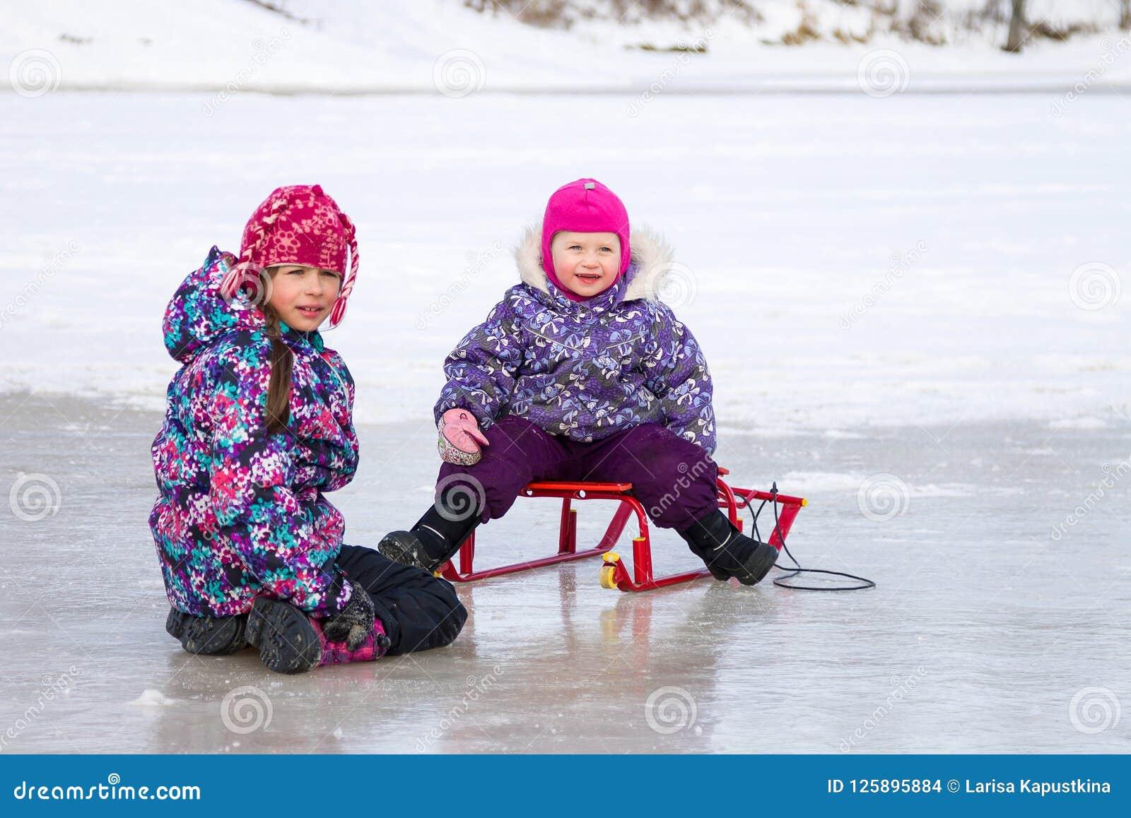 Twee jonge geitjes hebben samen pretzitting op het ijs en het spelen met een sneeuwslee op duidelijke de winterdag