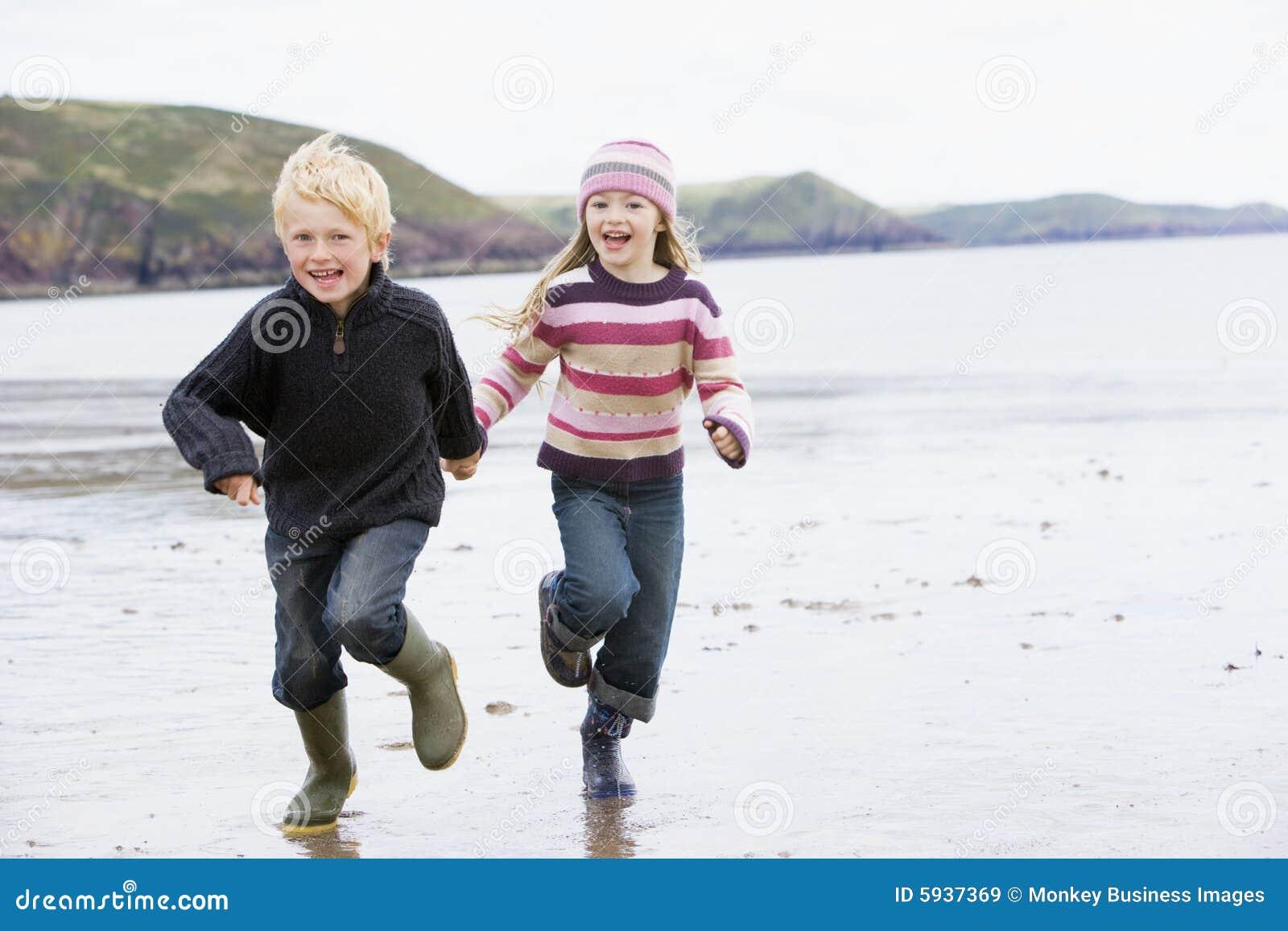 Twee jonge kinderen die op de handen van de strandholding lopen