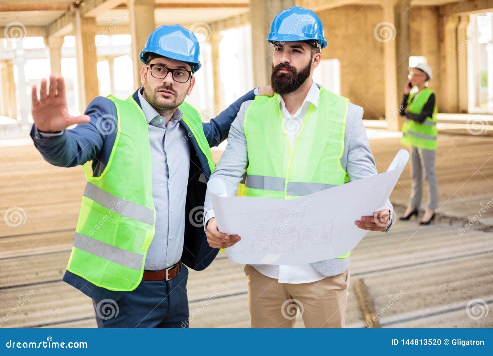 Twee jonge mannelijke ingenieurs die projectdetails op een bouwwerf bespreken