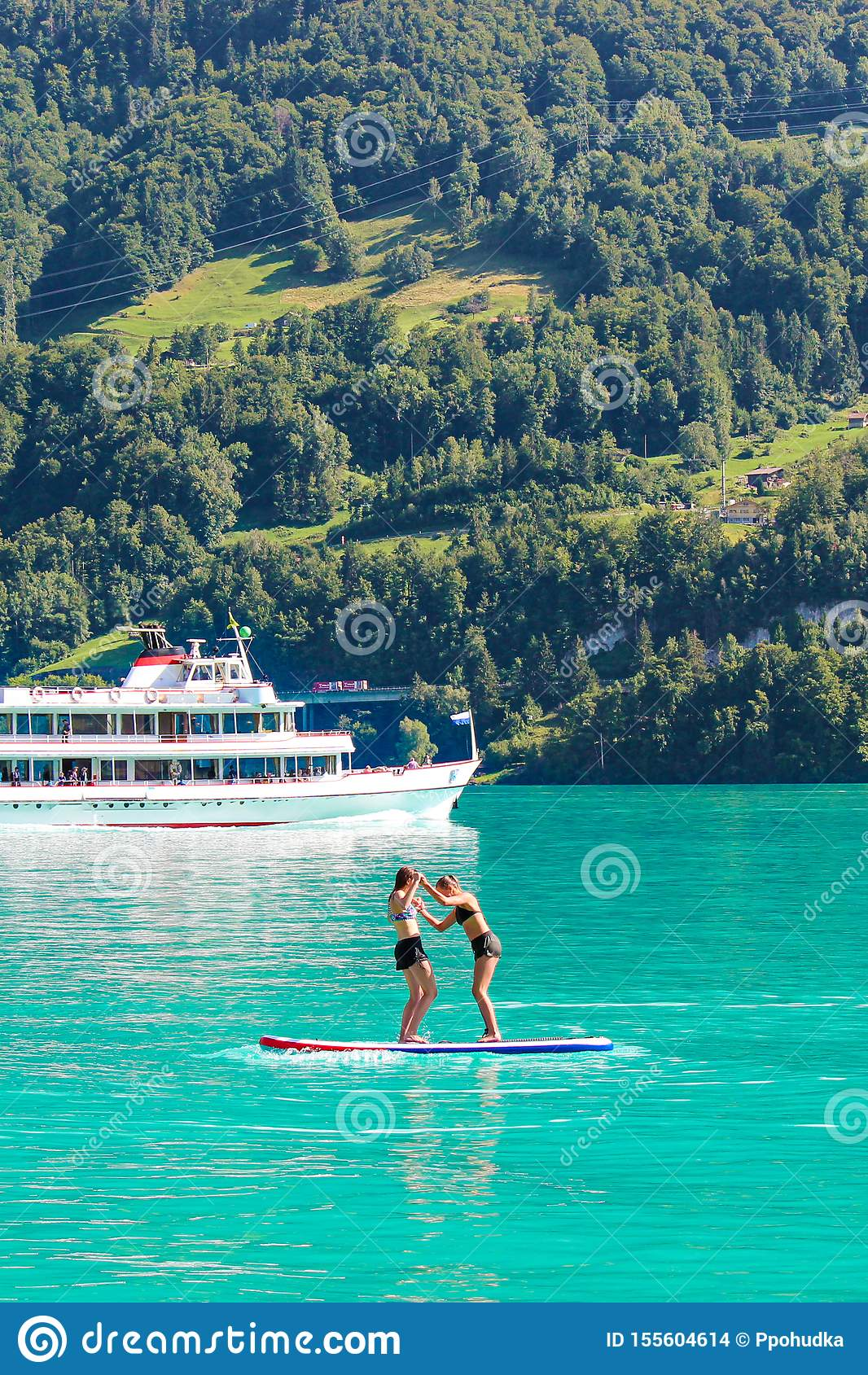 Twee jonge meisjesvrienden die zich op peddel bevinden schepen op turkoois Meer Brienz in Zwitserland in Toeristenboot op achterg