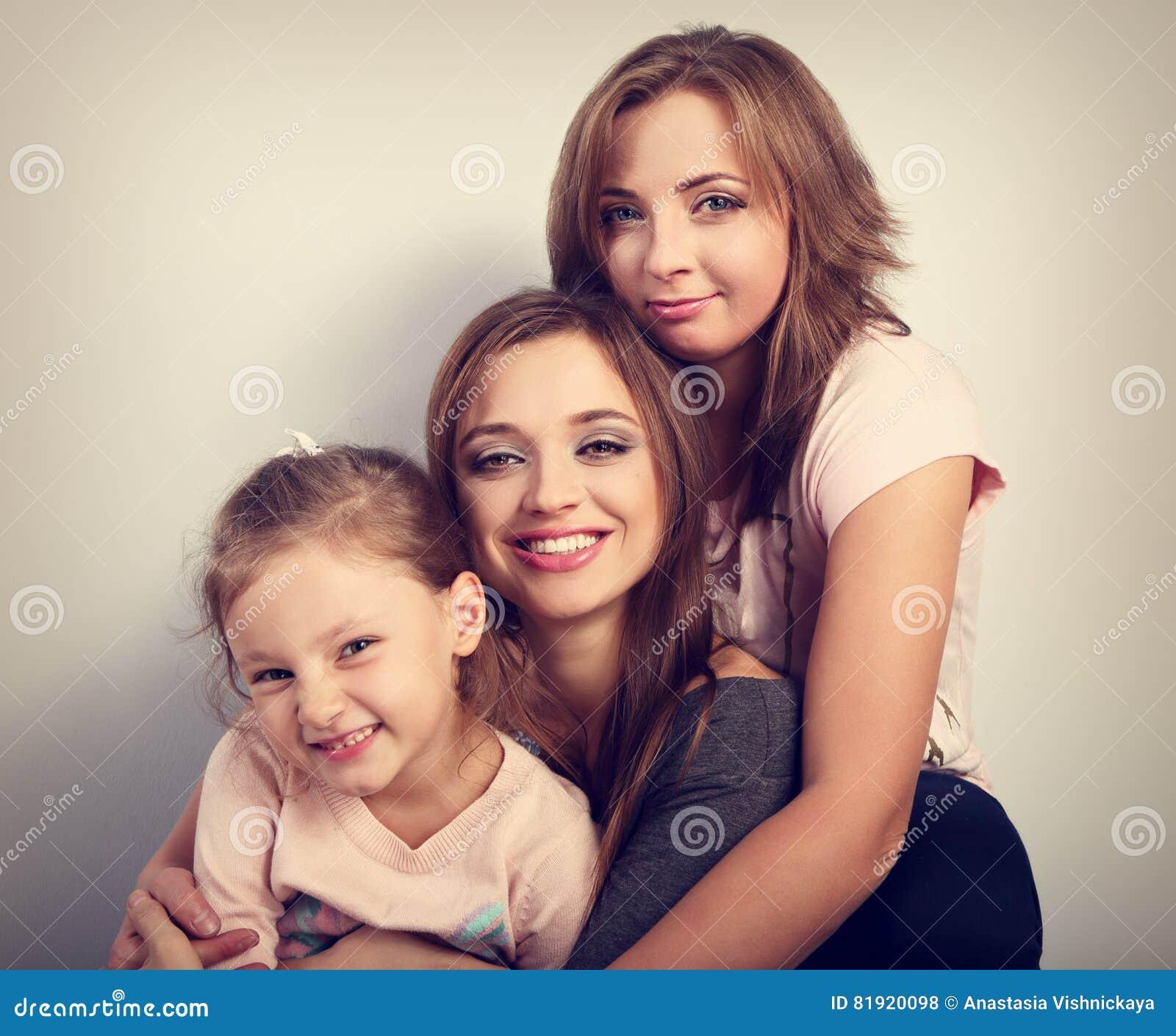 Twee jonge mooie glimlachende vrouwen en gelukkig joying jong geitjemeisje hugg