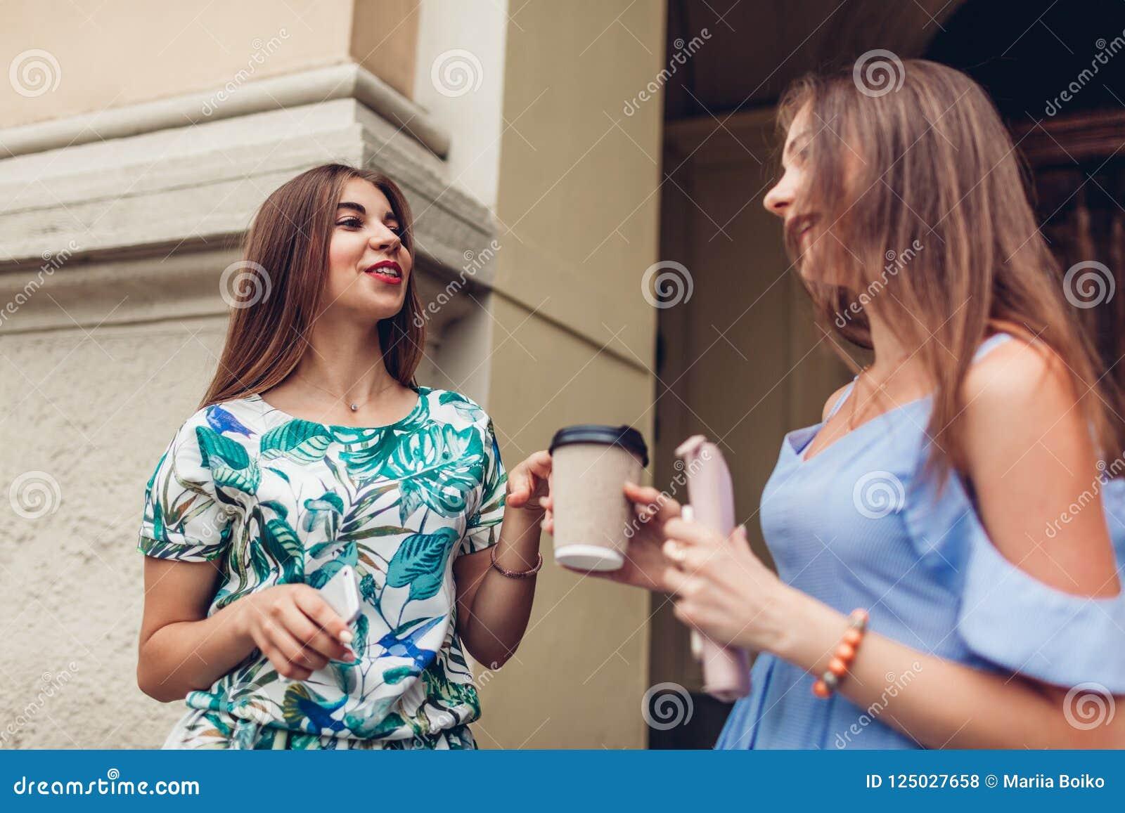 Twee jonge mooie vrouwen die het drinken koffie spreken Meisjes die pret in stad hebben De beste vrienden babbelen in openlucht
