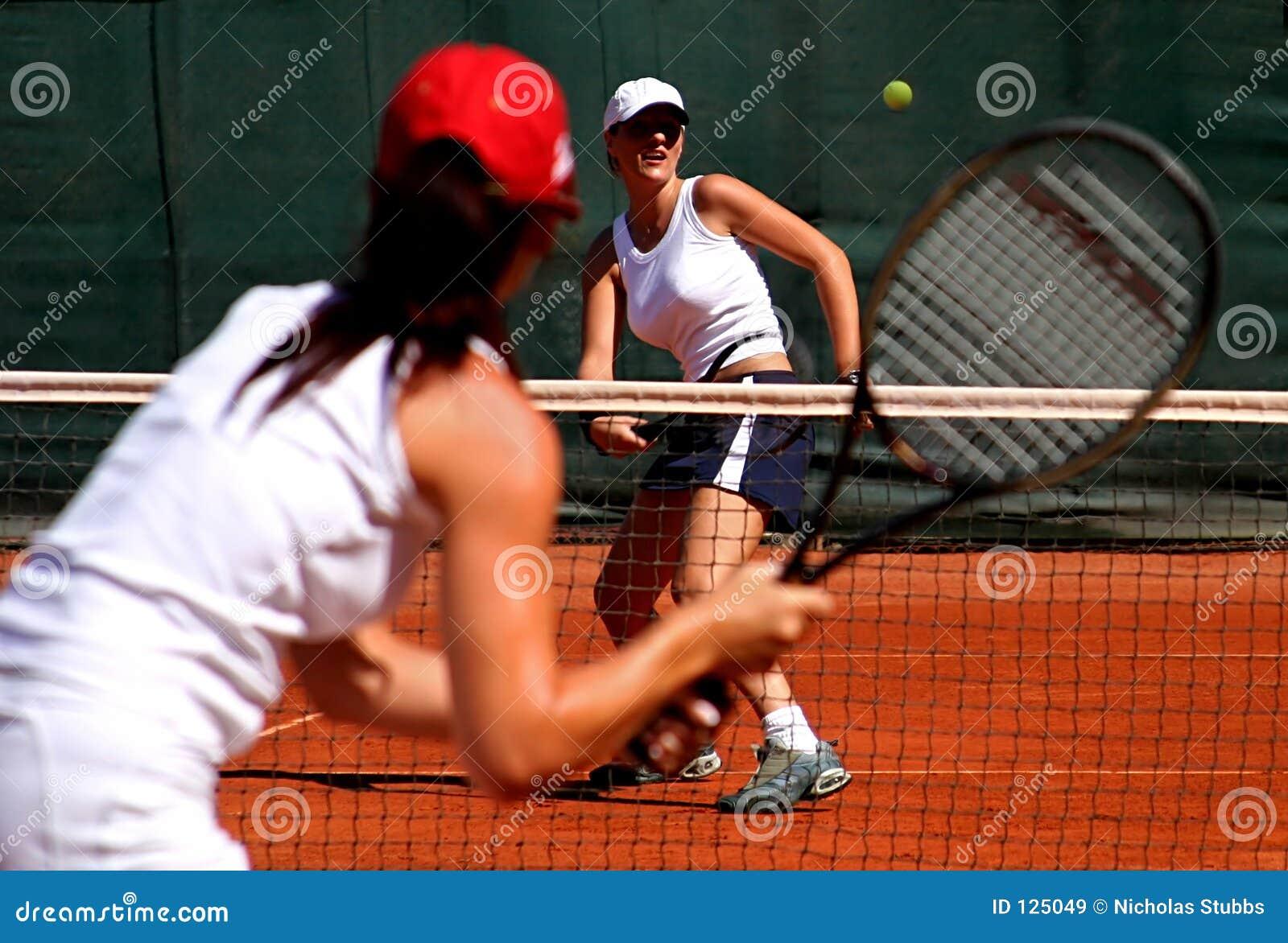 Twee jonge sportieve vrouwelijke tennisspelers die een spel in de zon hebben.