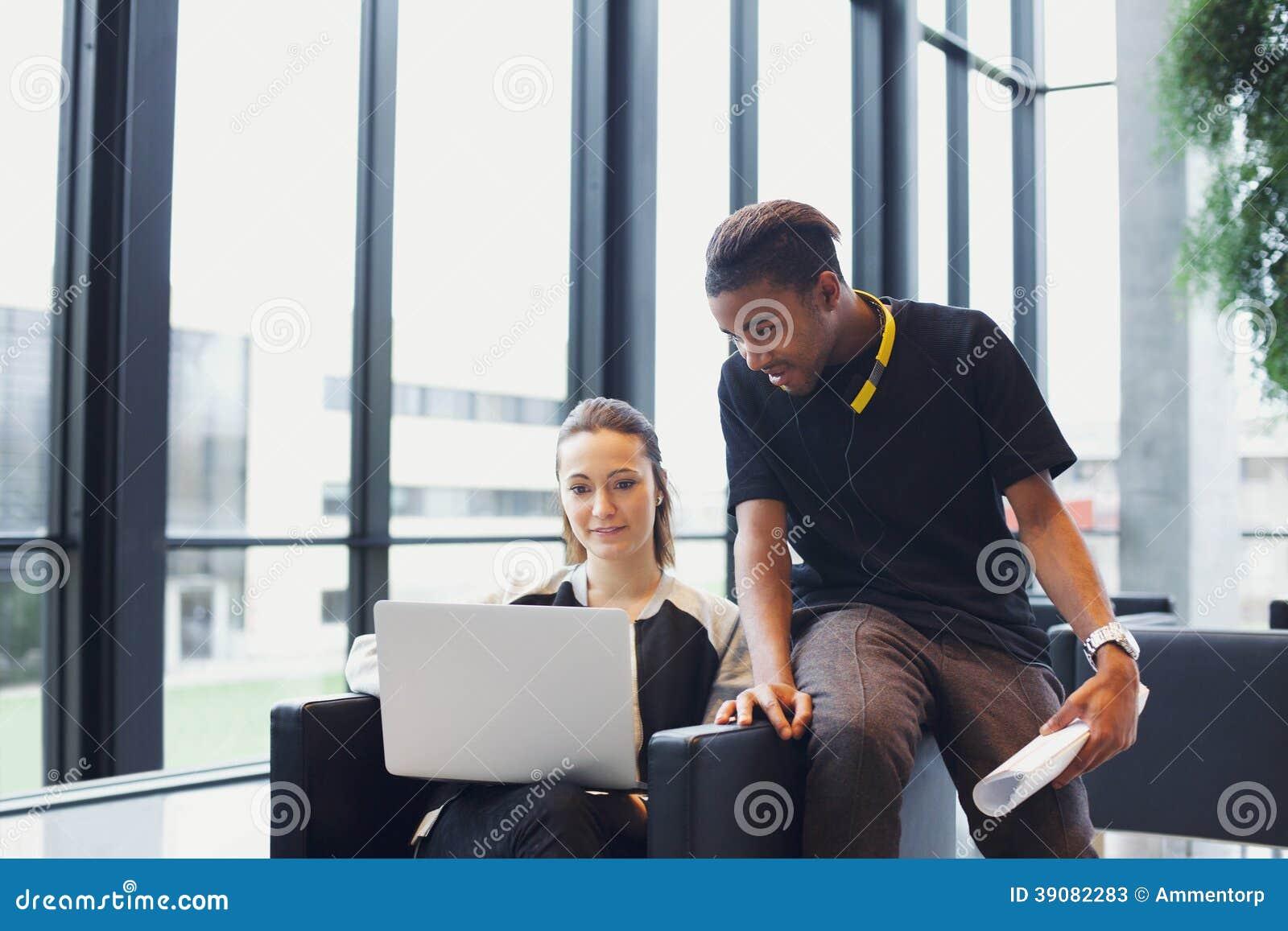 Twee jonge studenten die laptop in campus met behulp van