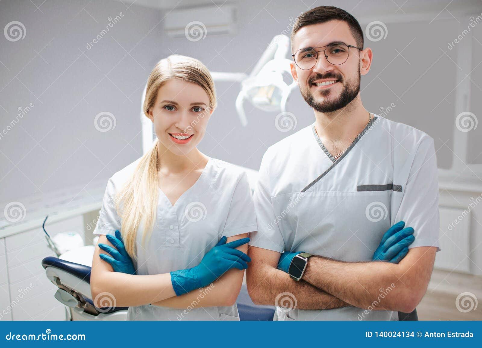 Twee jonge tandartsberoeps in tandheelkunderuimte Zij stellen op camer en glimlach De mensen houden handen gekruist