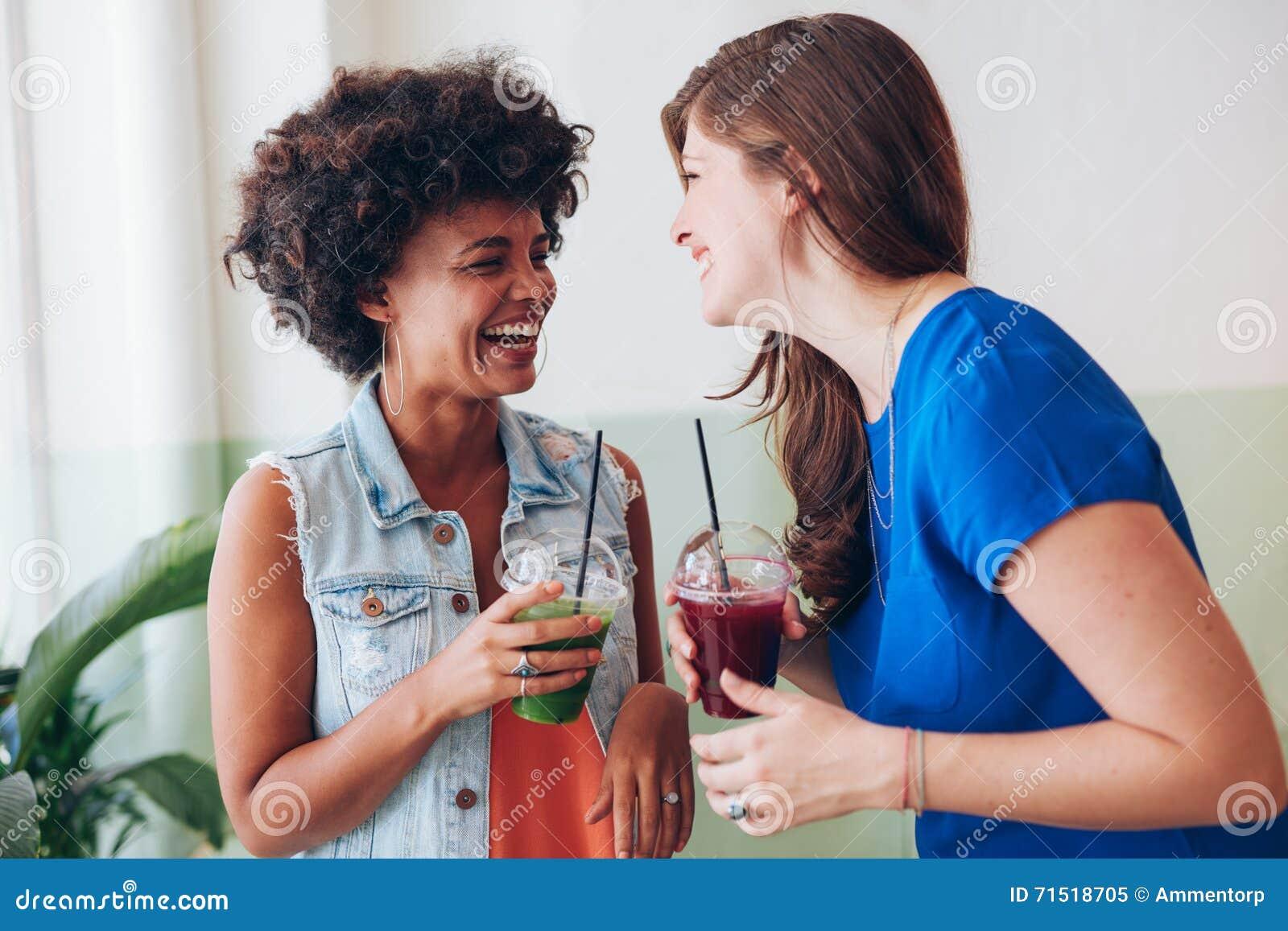 Twee jonge vrienden die vers sap en het spreken hebben