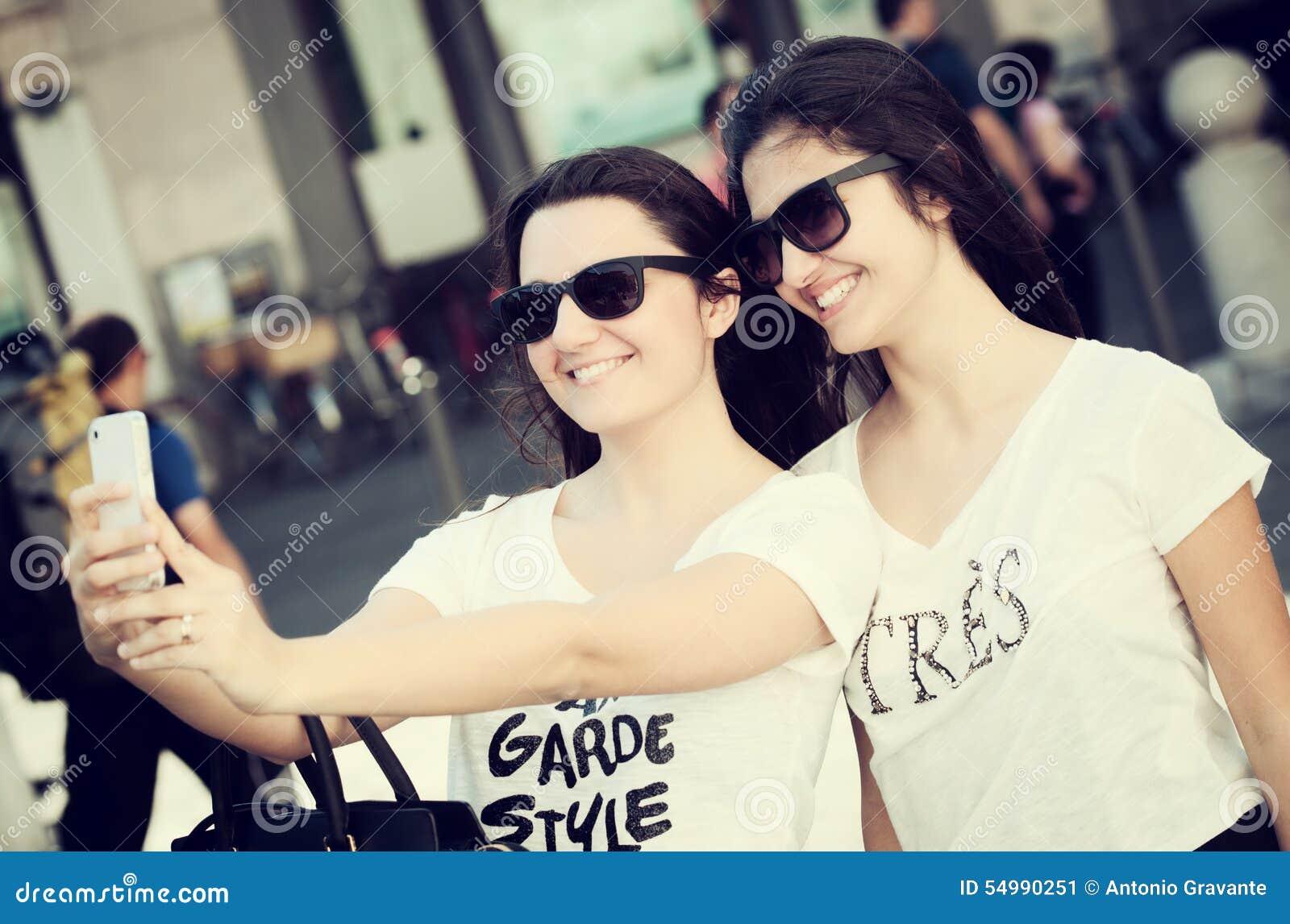 Twee jonge vrouwen die een selfie met de slimme telefoon nemen