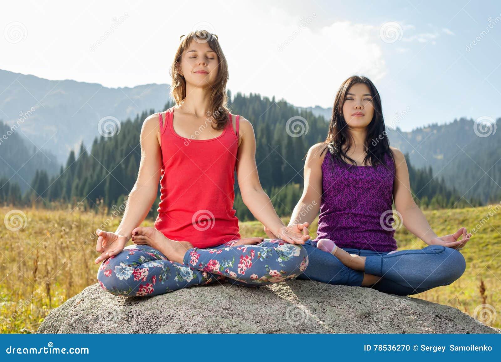 Twee jonge vrouwen die yoga op een rots doen