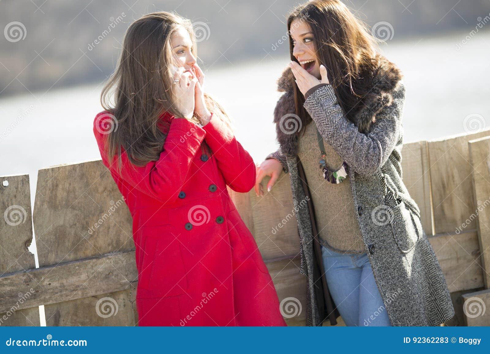 Twee jonge vrouwen die zich naast omheining, één van hen in een rood bevinden