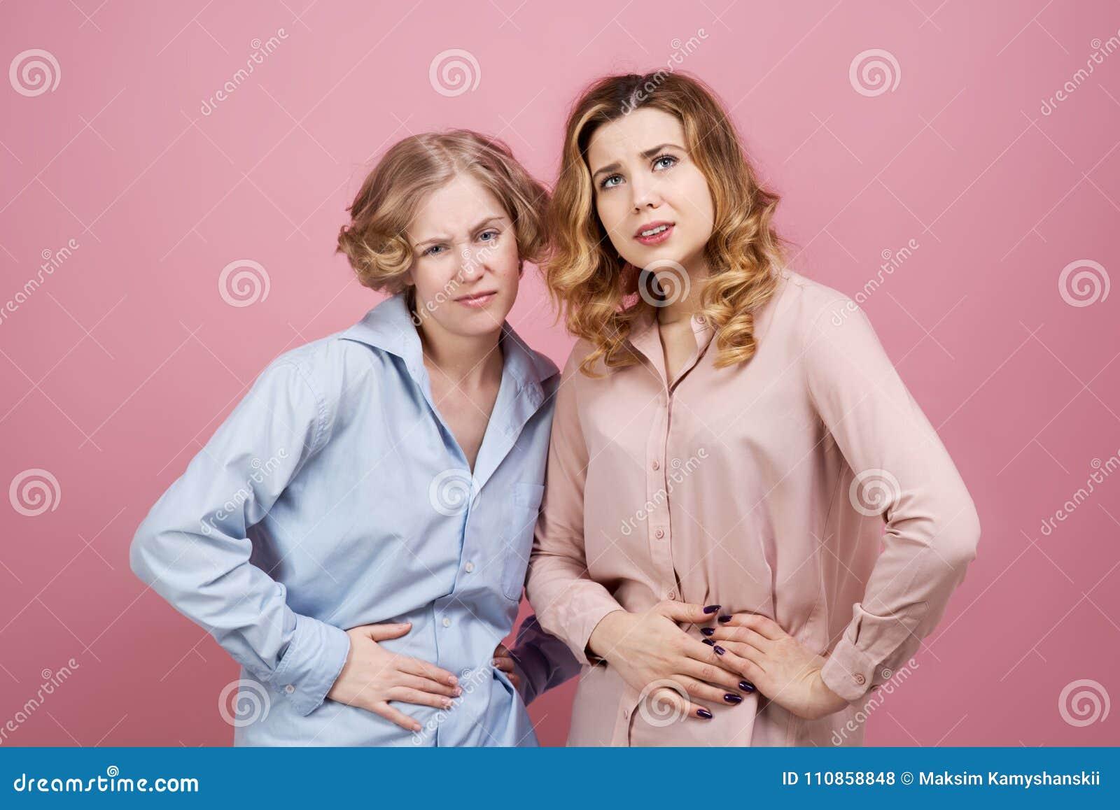 Twee jonge vrouwengreep op hun buiken met het lijden van aan uitdrukking Studioportret op roze achtergrond