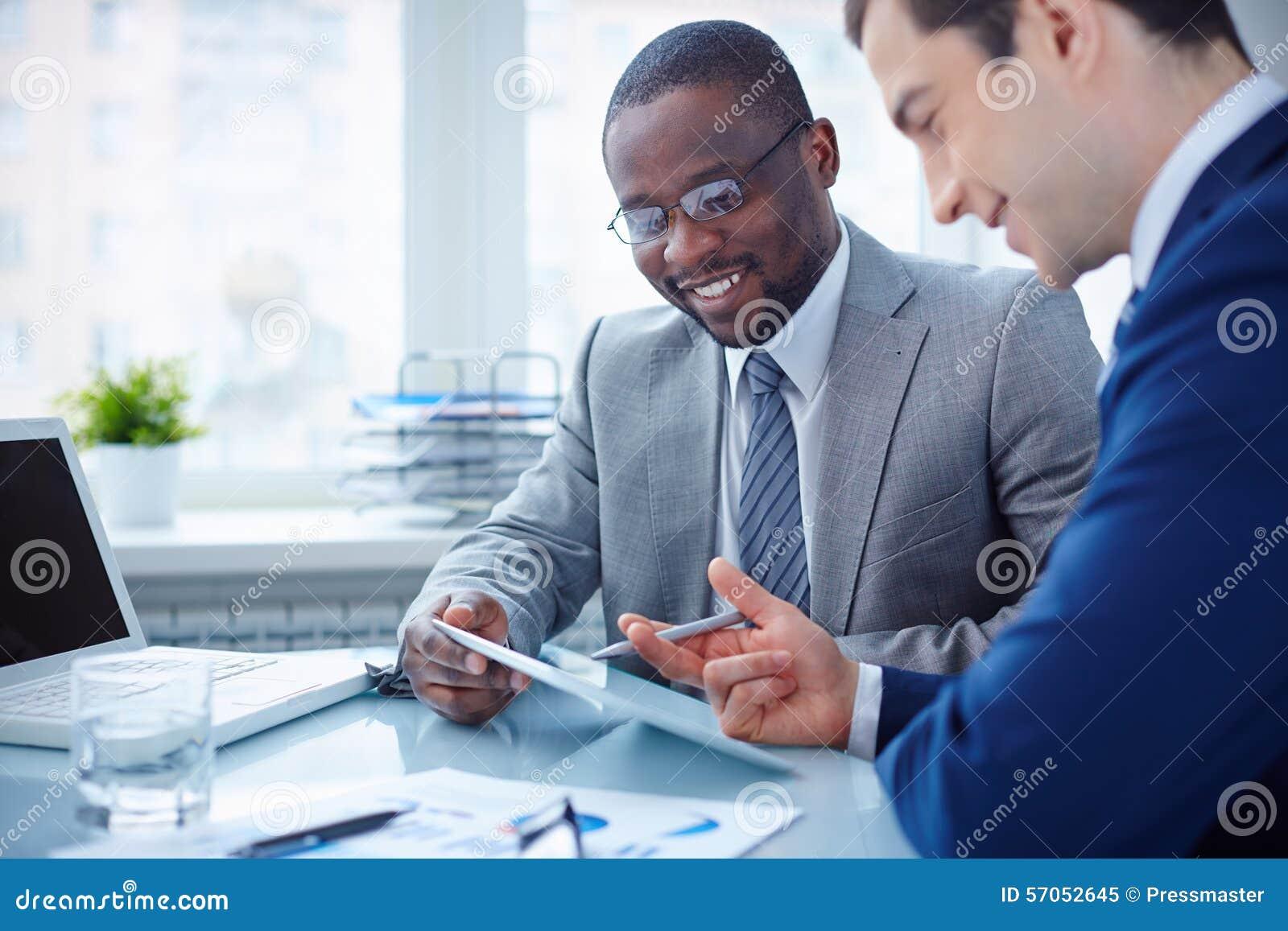 Twee jonge zakenlieden die over zaken spreken terwijl één van hen die op de computer leunen controleert