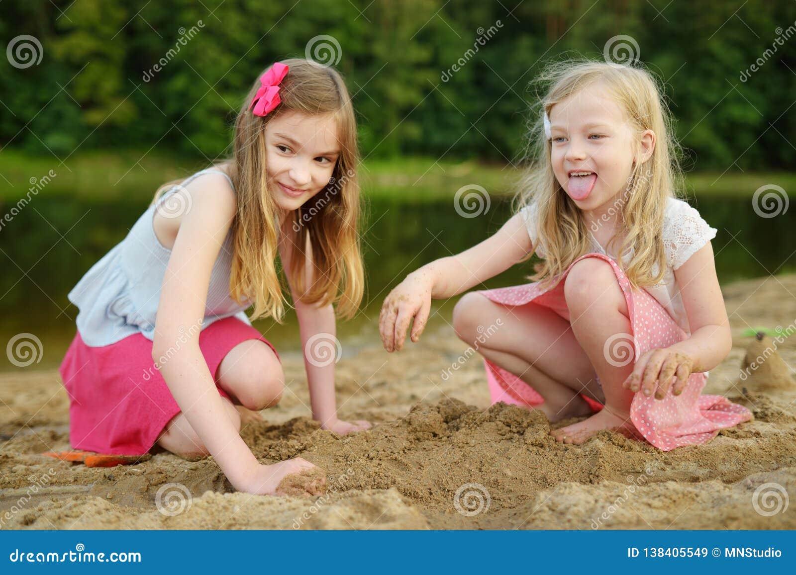 Twee jonge zusters die pret op een zandig meerstrand hebben op warme en zonnige de zomerdag Jonge geitjes die door de rivier spel