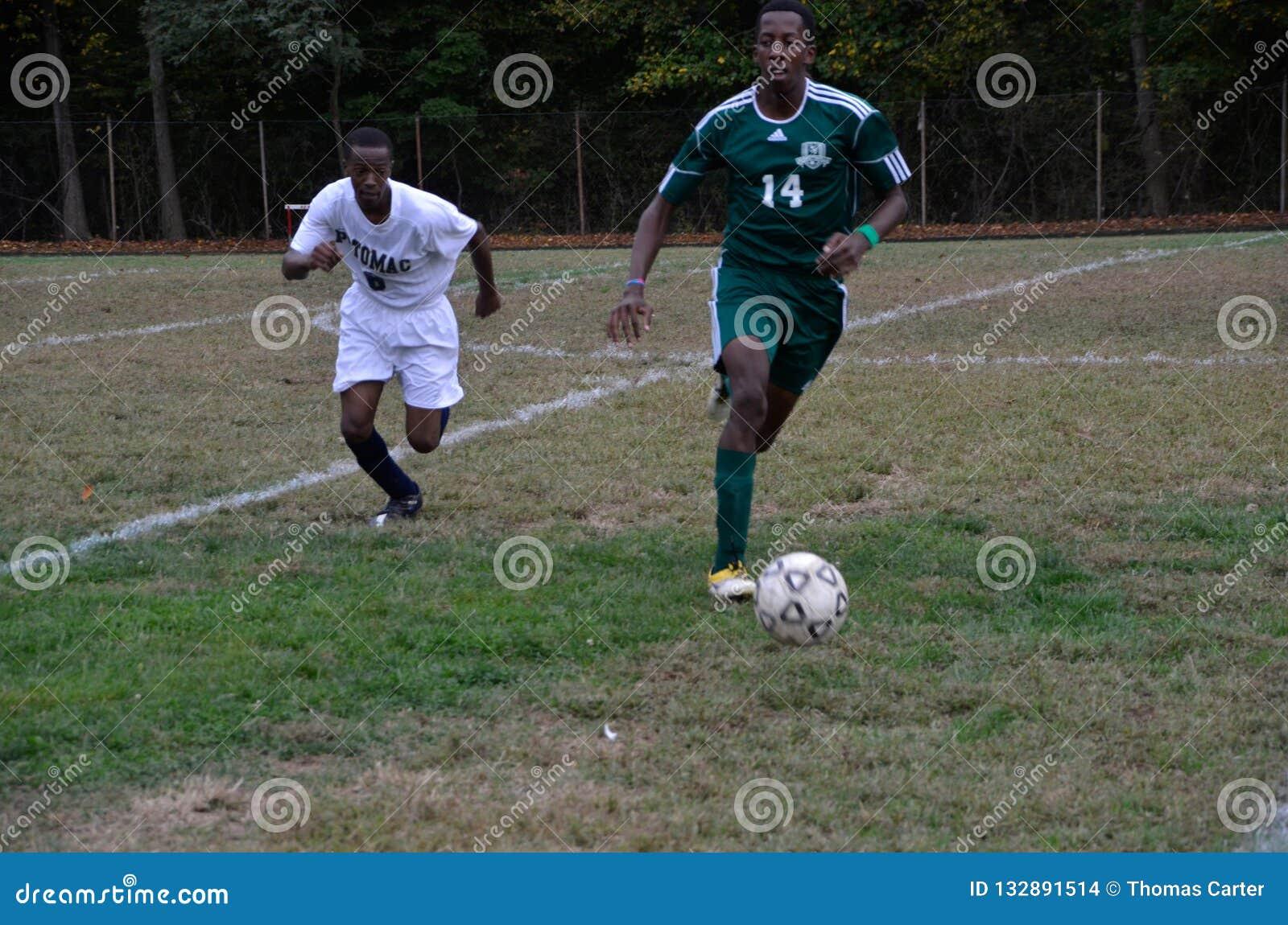 Twee jongens die middelbare schoolvoetbal spelen