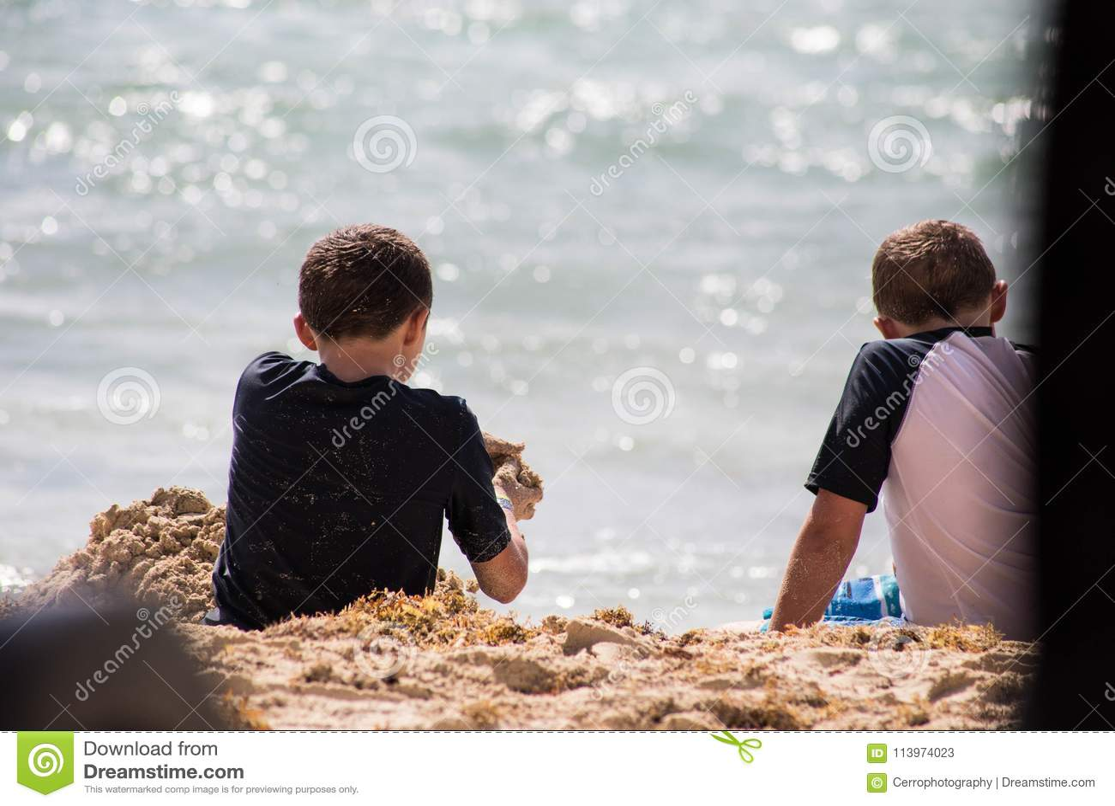 Twee jongens speels op vakantie op het strand met zand op een hete de zomerdag