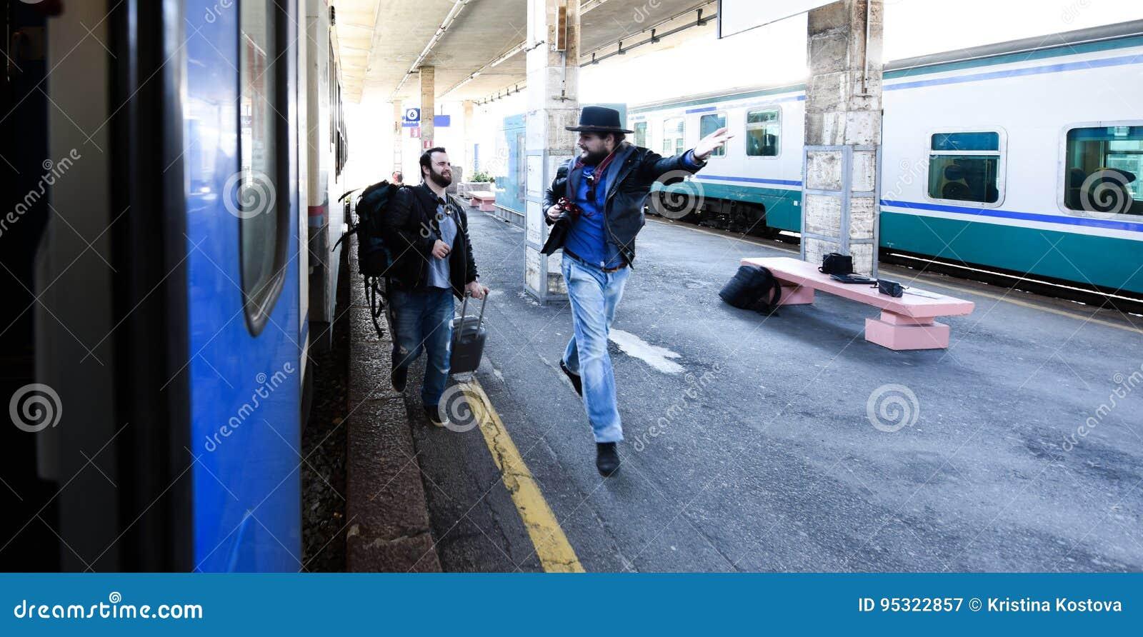 Twee kerels zijn laat voor de trein en het lopen om het te vangen Één van hen wordt verspild